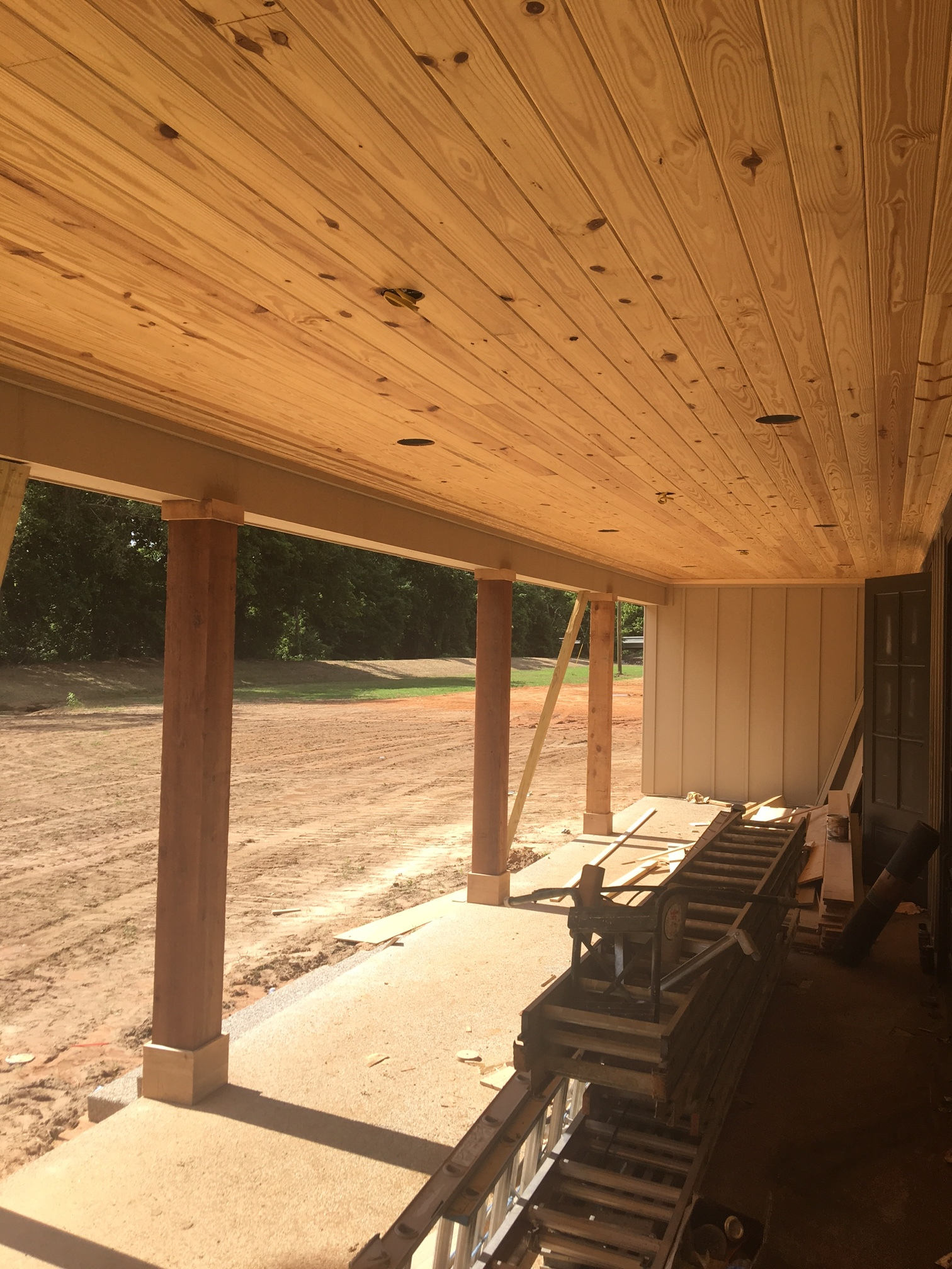 Covered side porch overlooking courtyard (columns getting stained and ceiling getting painted)
