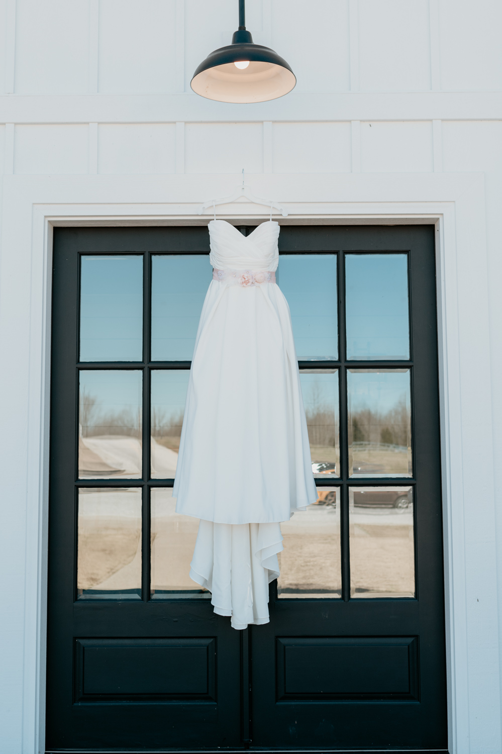 wedding dress in front of black doors .jpg