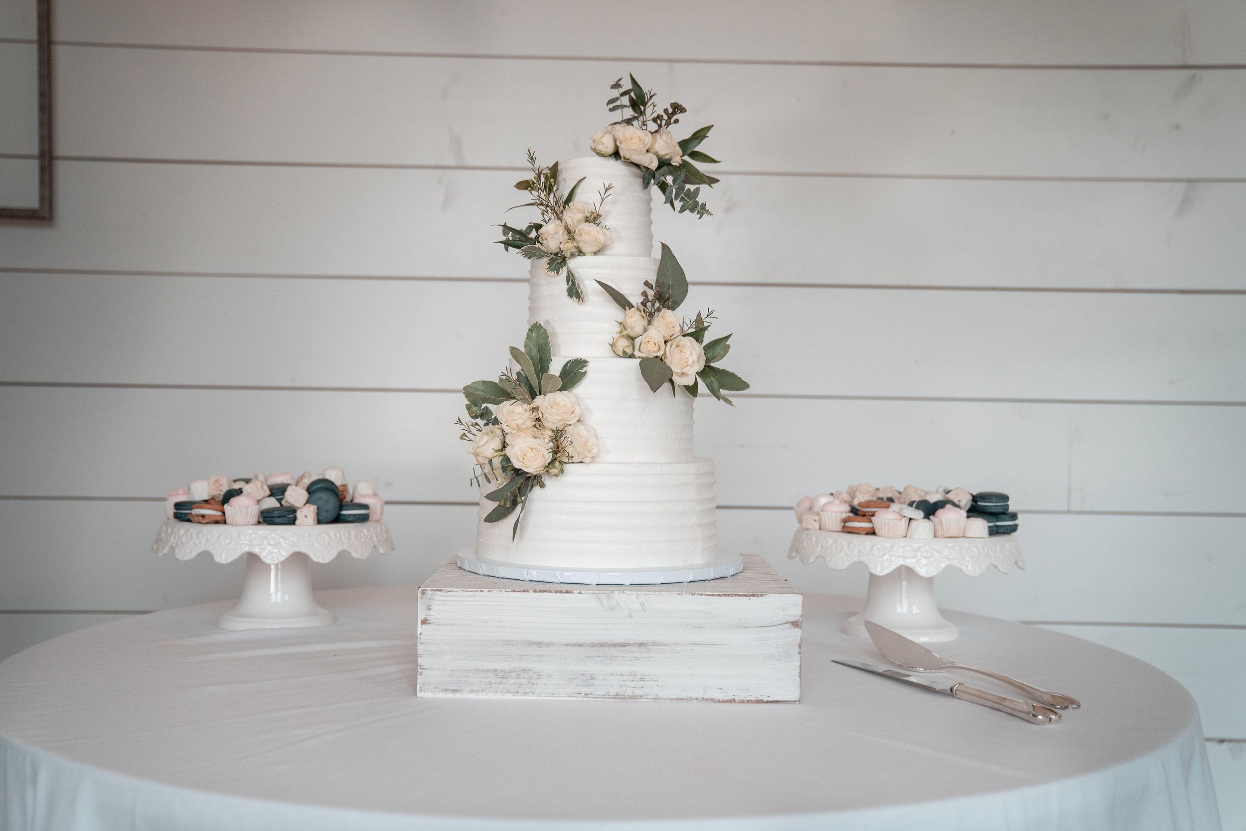 wedding cake infront of white shiplap wall.jpg