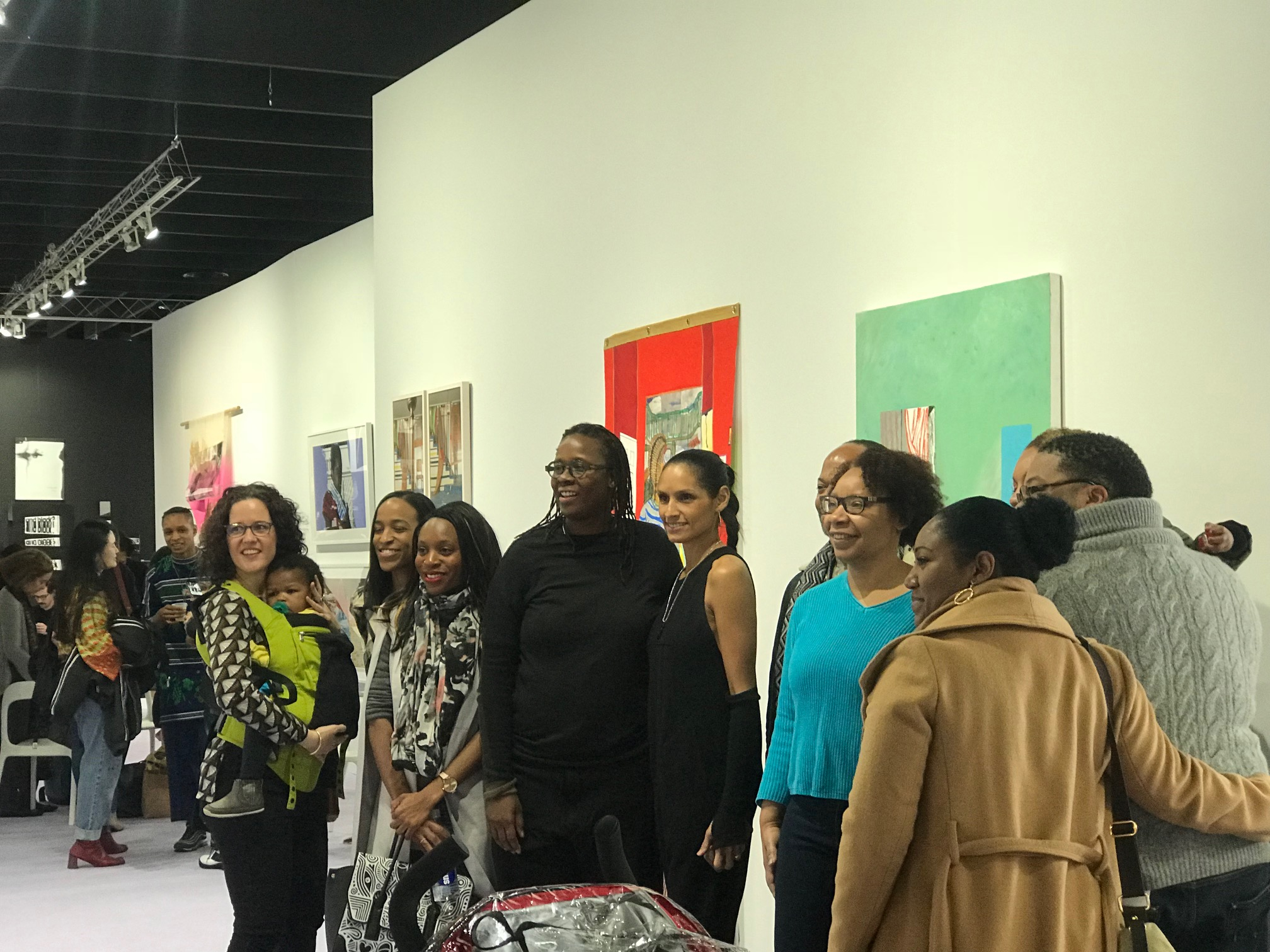 Mickalene & Racquel taking a photo with a group on tour of the curated section