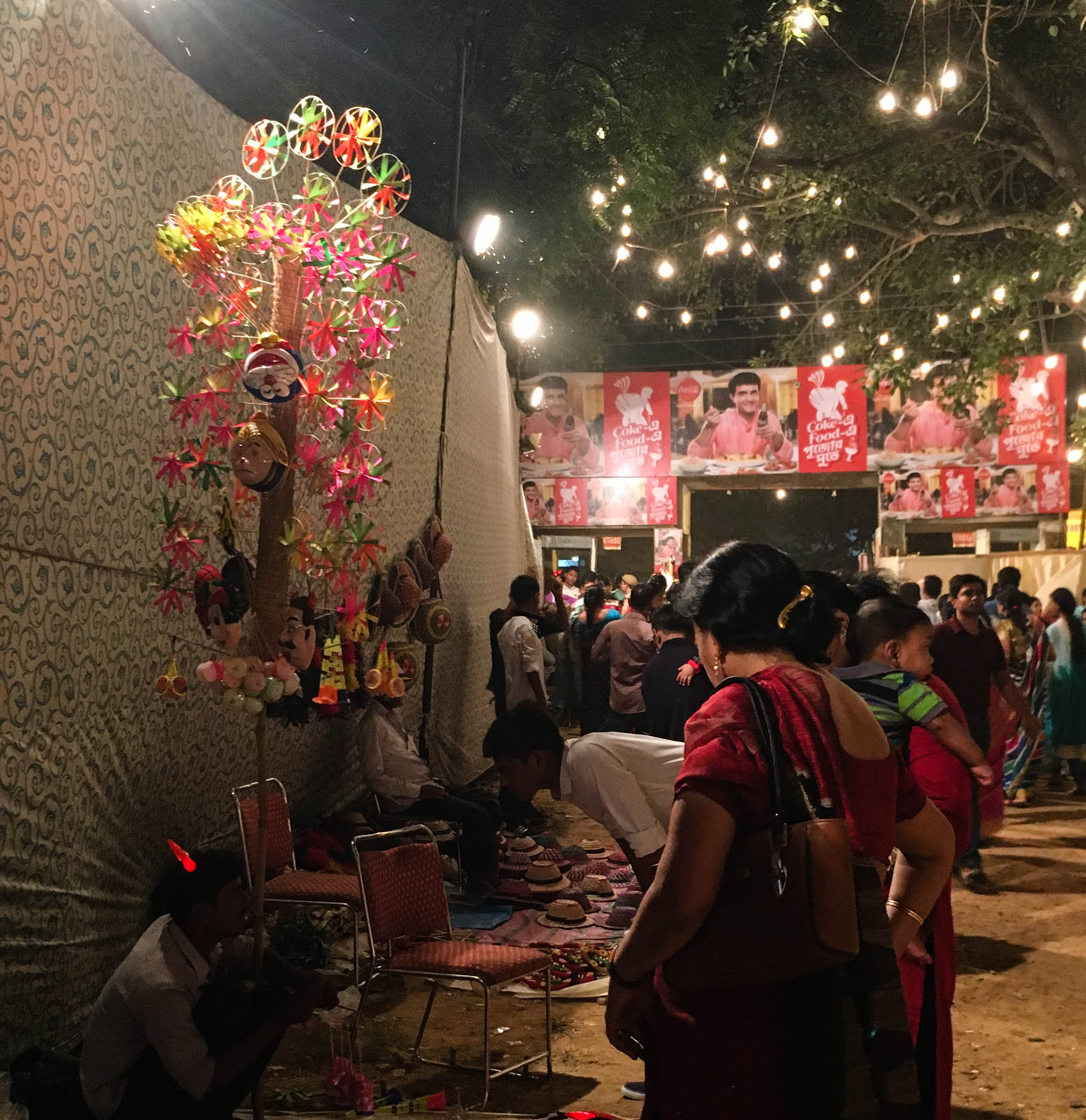 The goddess has vanquished  Mahishasur, but the red-horned fan seller poses a little problem: to buy or not to buy yet another fan?