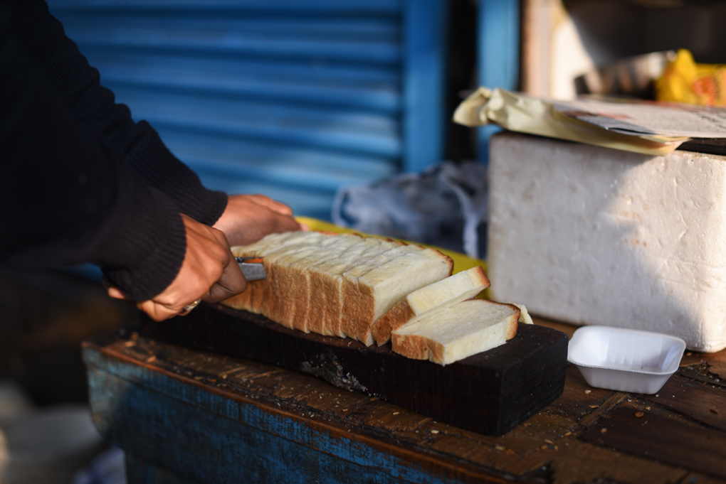 Freshly baked bread is sliced,    toasted, buttered and sprinkled with sugar, to be dipped in chai and devoured.