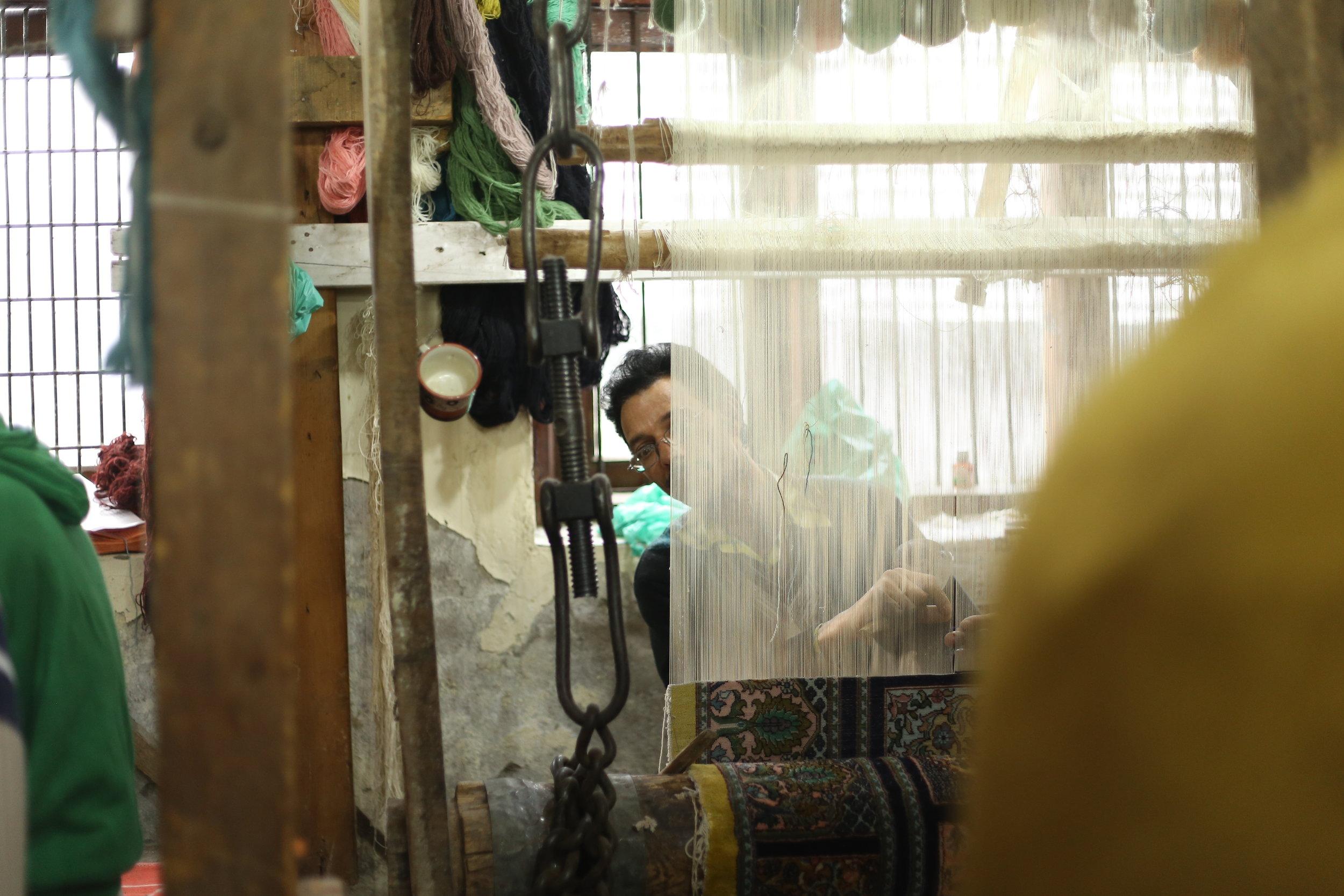 A weaver looks through his WIP.