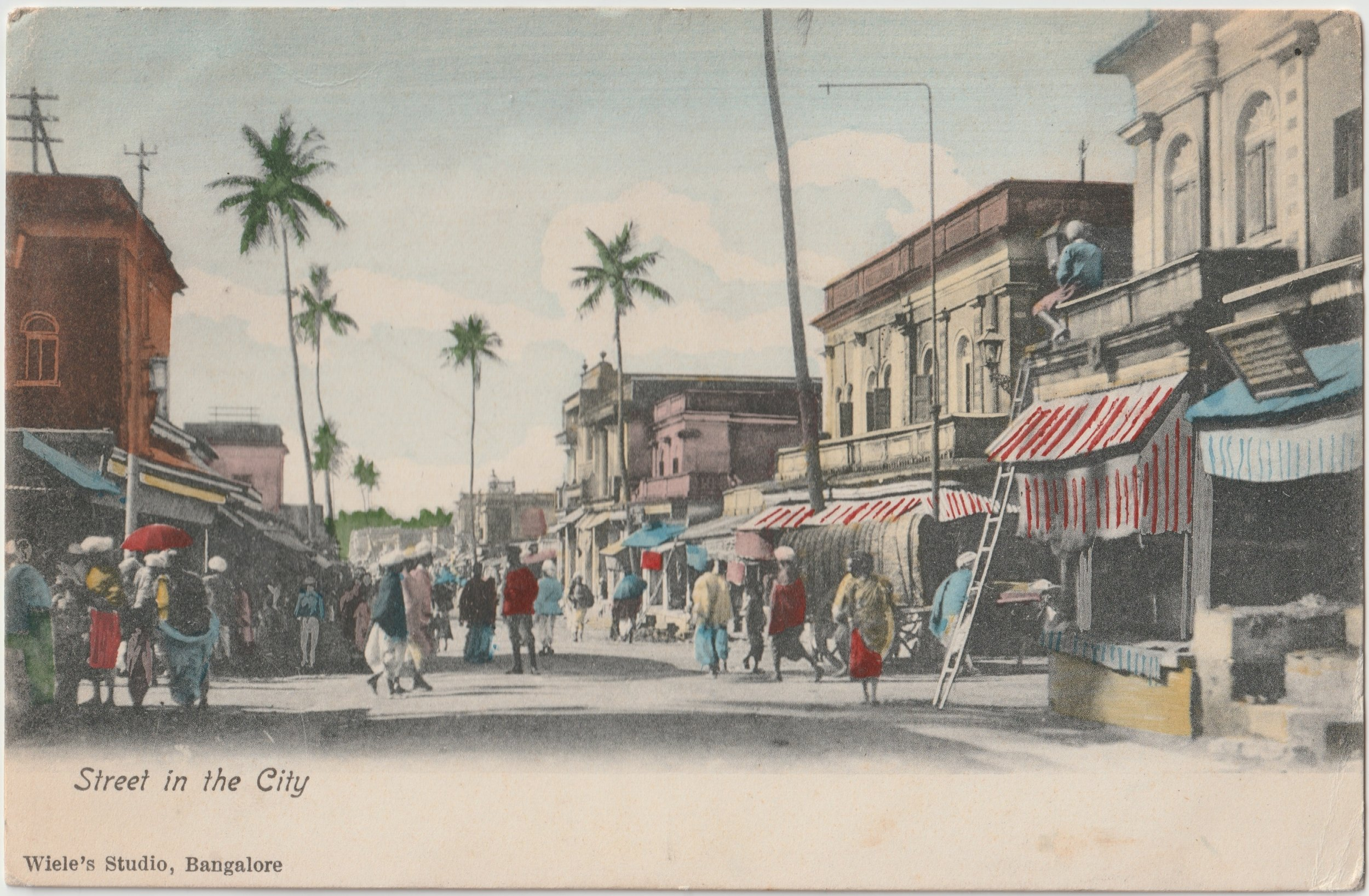 """Street in the City"". Published by Wiele's Studio, Bangalore. Posted on: 31.01.1907.    Message reads:  after I finish my mail Ella asks me to say regarding photo enclosed that it is a puzzle photo and the puzzle is to find Ella Brown """