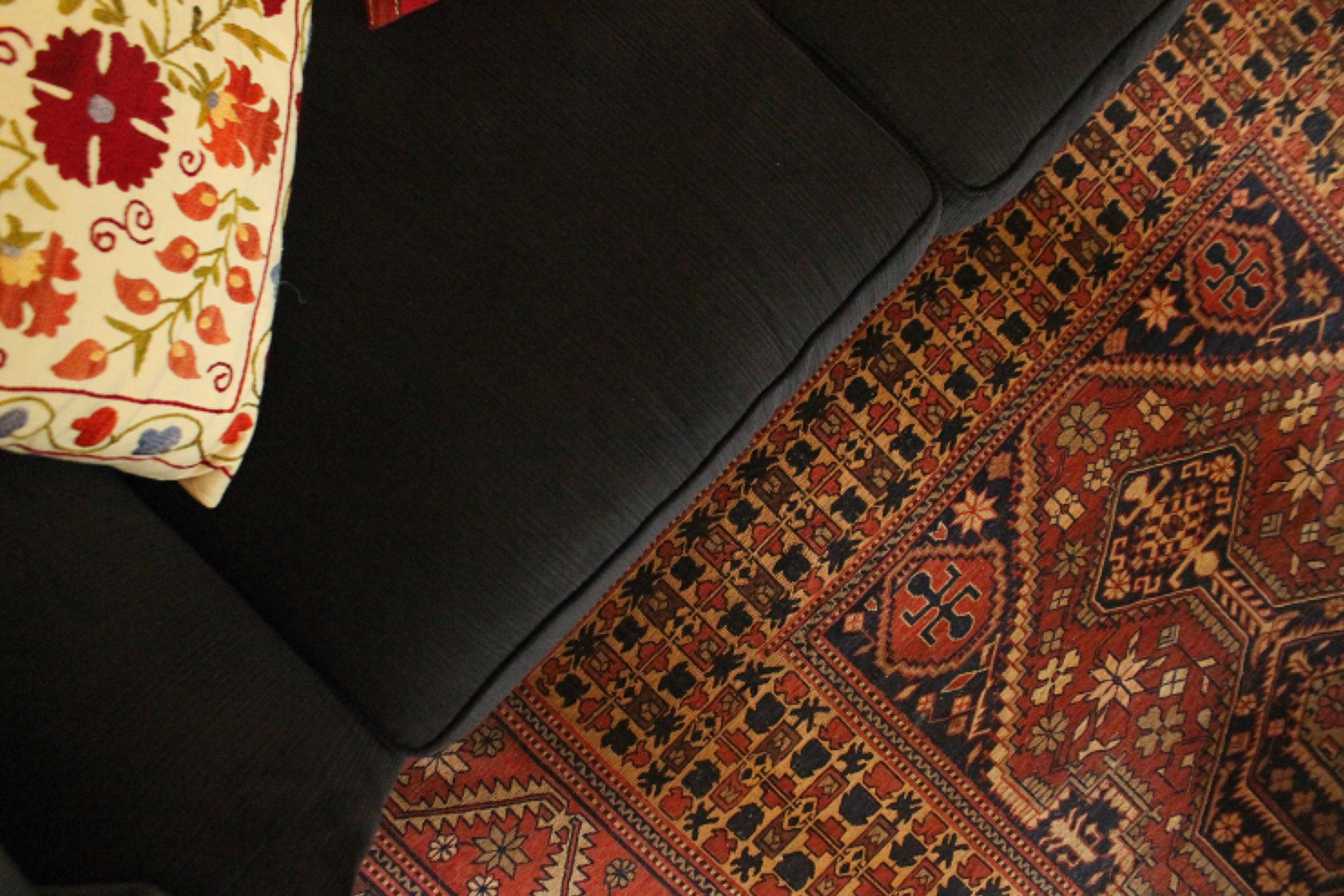 Ethnic pattern pada karpet dan cushion cover dengan latar sofa gelap polos