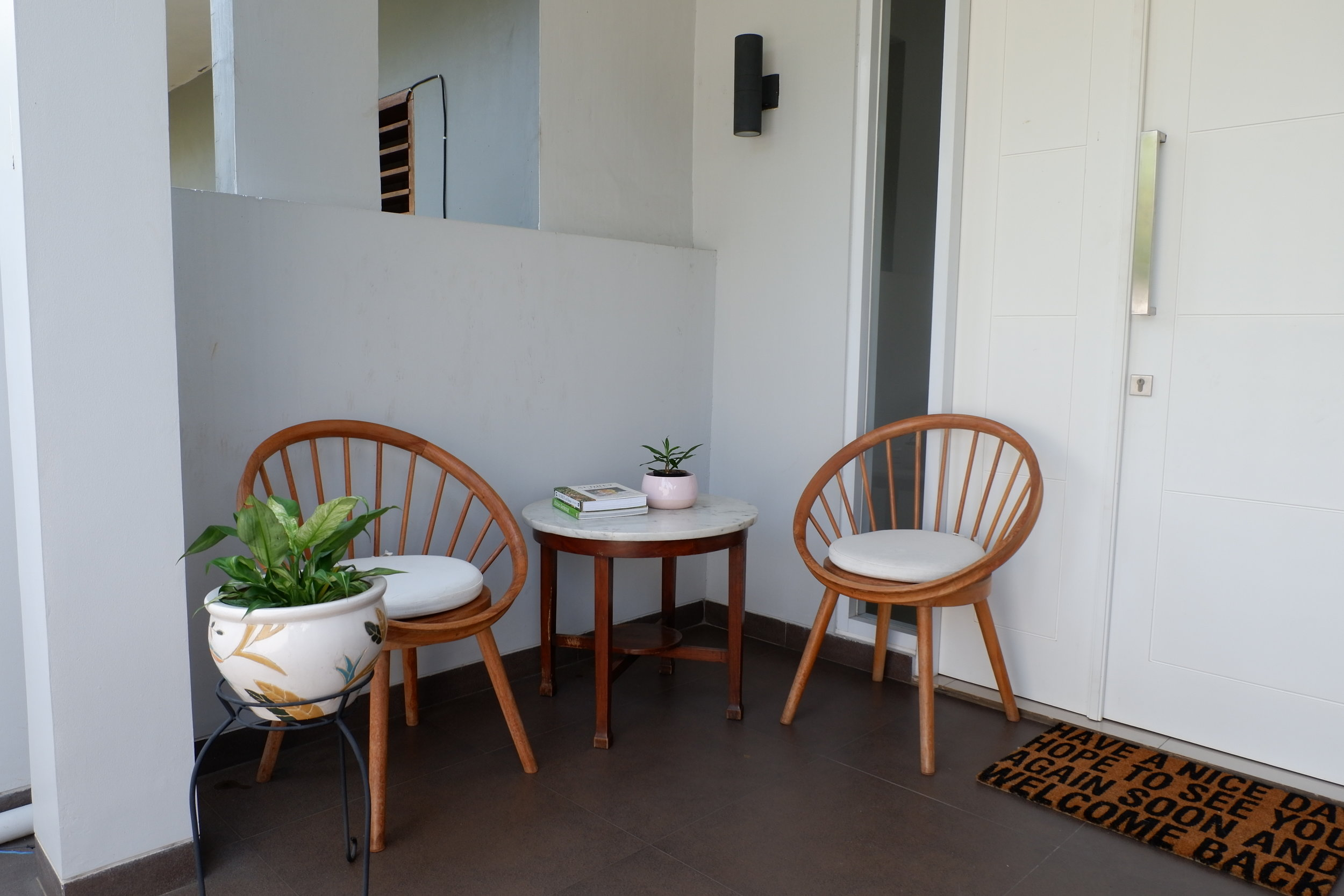 Sepasang kursi kayu dan tanaman hijau yang meromantiskan teras di sore hari