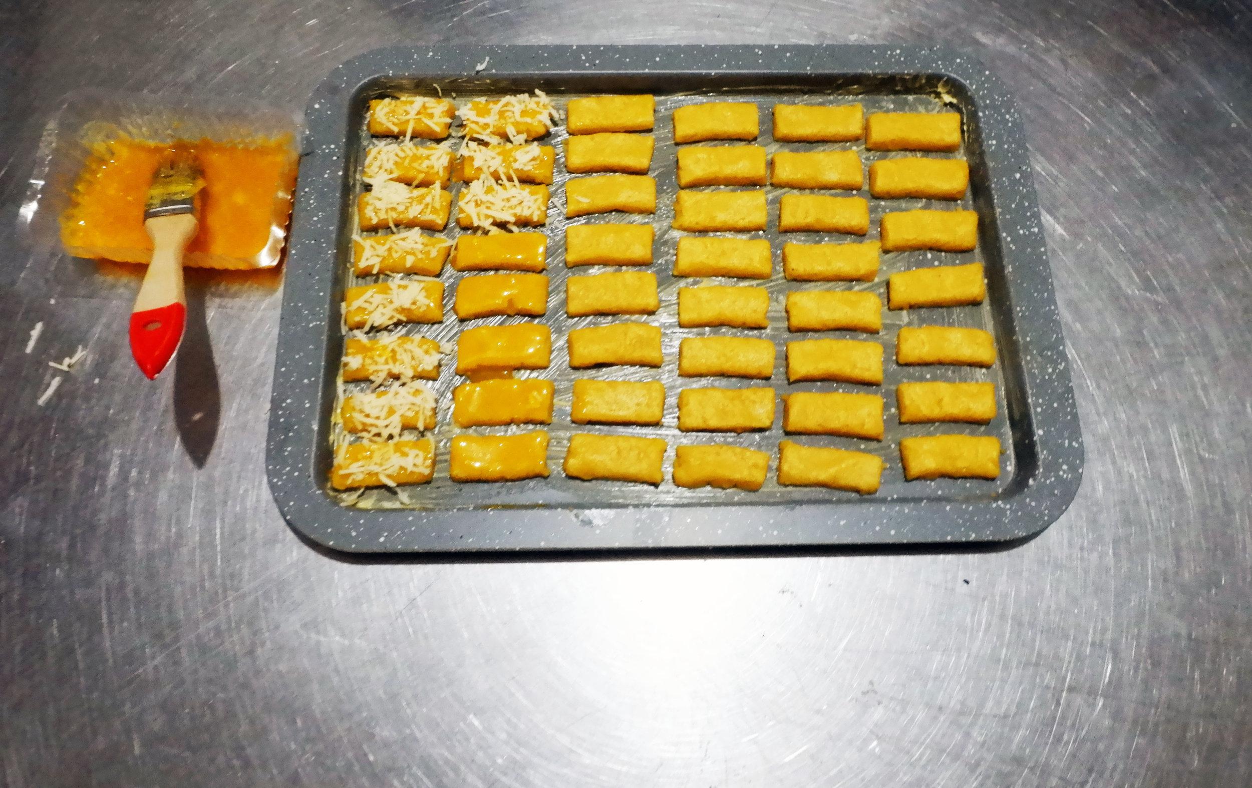- Oleskan kuning telur pada adonan tersebut, kemudian taburi parutan keju pada bagian atas adonan secukupnya.