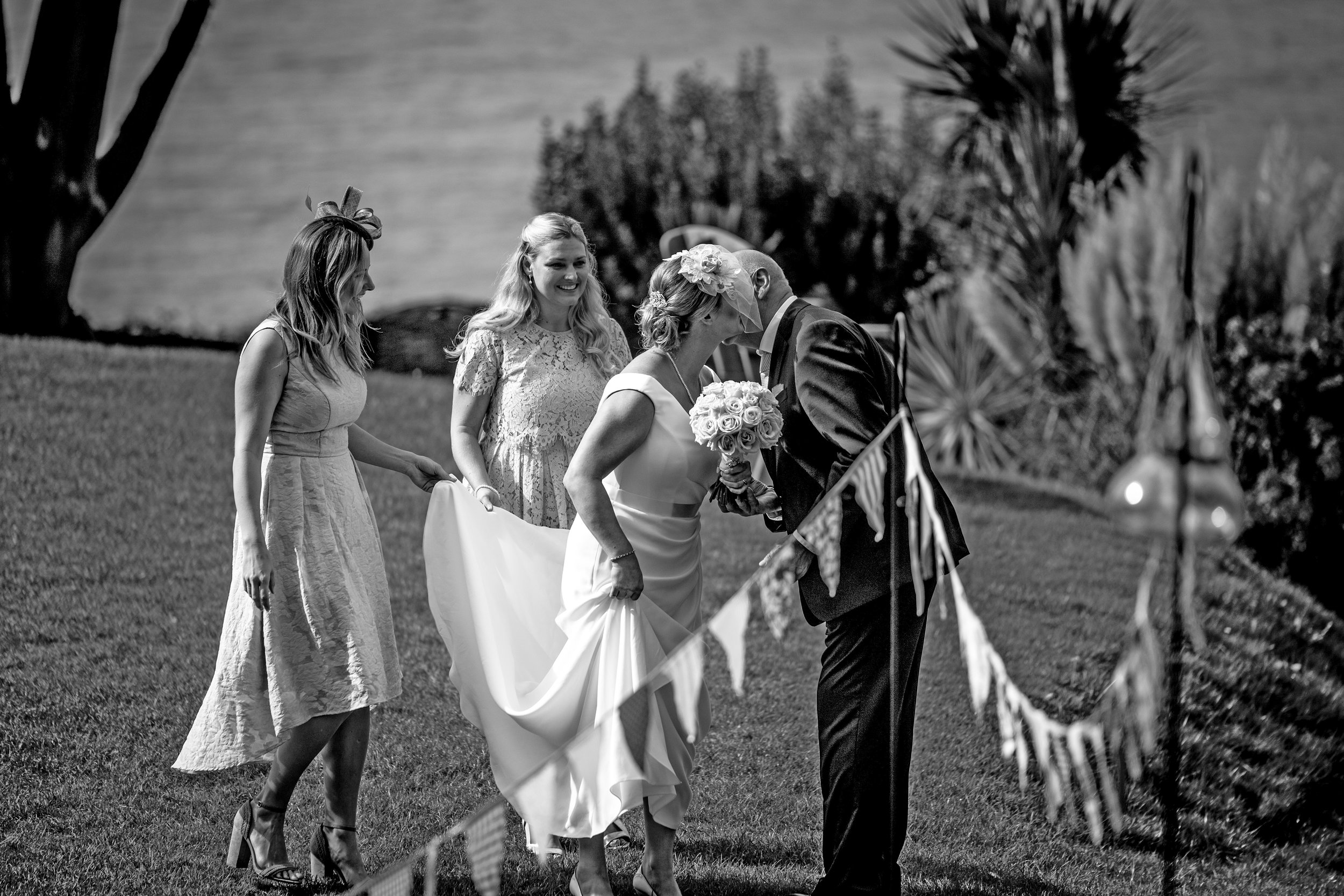 The father of the bride greets his daughter (The Bride) as she arrives for the wedding ceremony with her bridesmaids. Photo by Cambridge Reportage wedding photographer Nia & James The Photographers