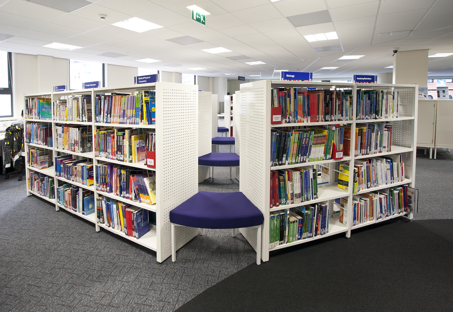 White Aspire shelving separated by seating pads creating alternative display options
