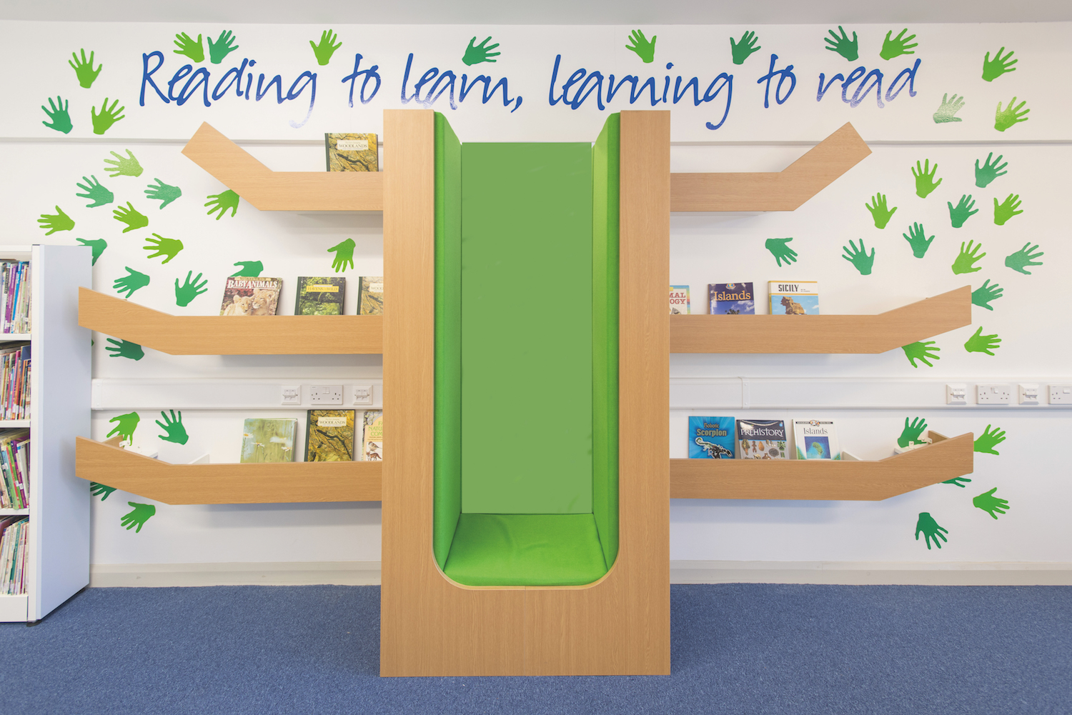 Woodland themed reading booth with vinyl hand prints in shades of green, mimicking tree leaves.