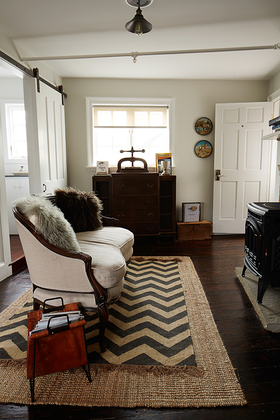 James Louis sitting area with loveseat and wood burning stove.