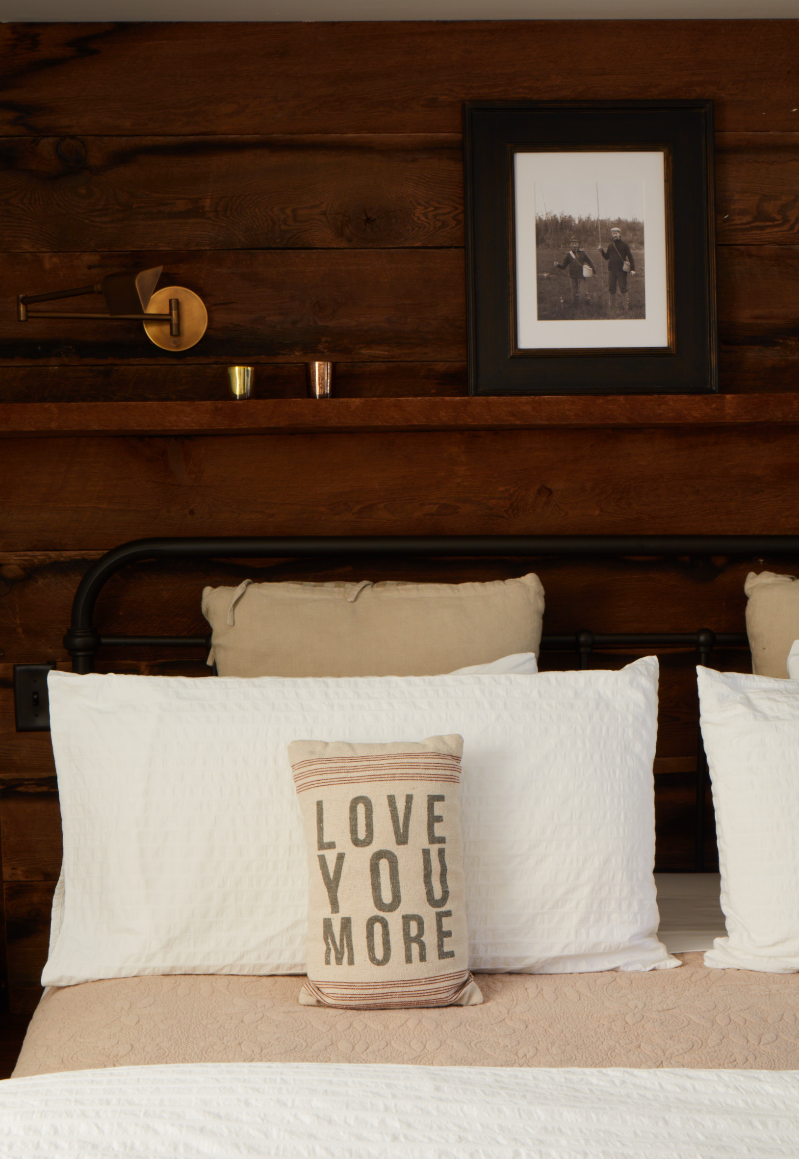 "The Lee Wendell Suite - ""Love you More"" pillow on bed and reclaimed wood wall"