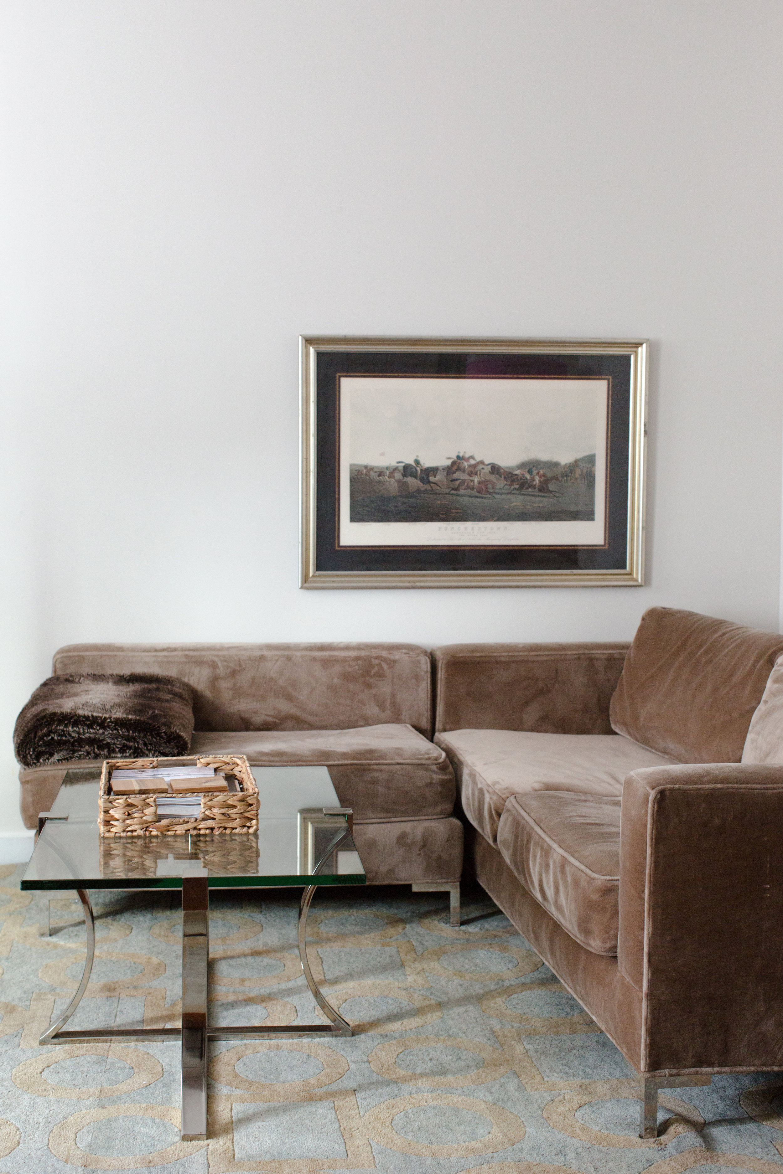 The Pint living room with framed art, glass coffee table and brown L-shaped velvet couch