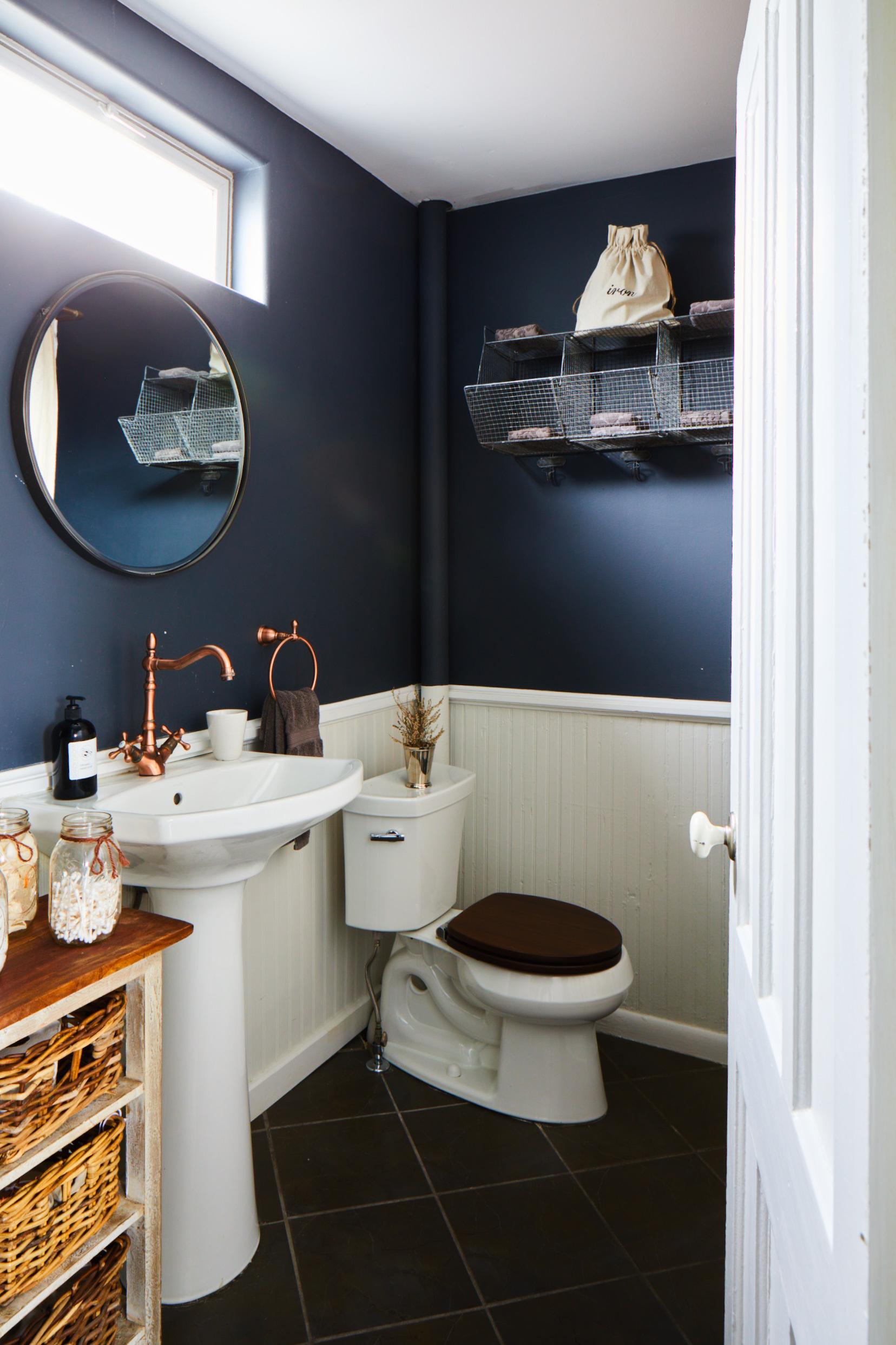 The Kemp bathroom with pedestal sink, toilet and navy blue walls with white wainscoting.