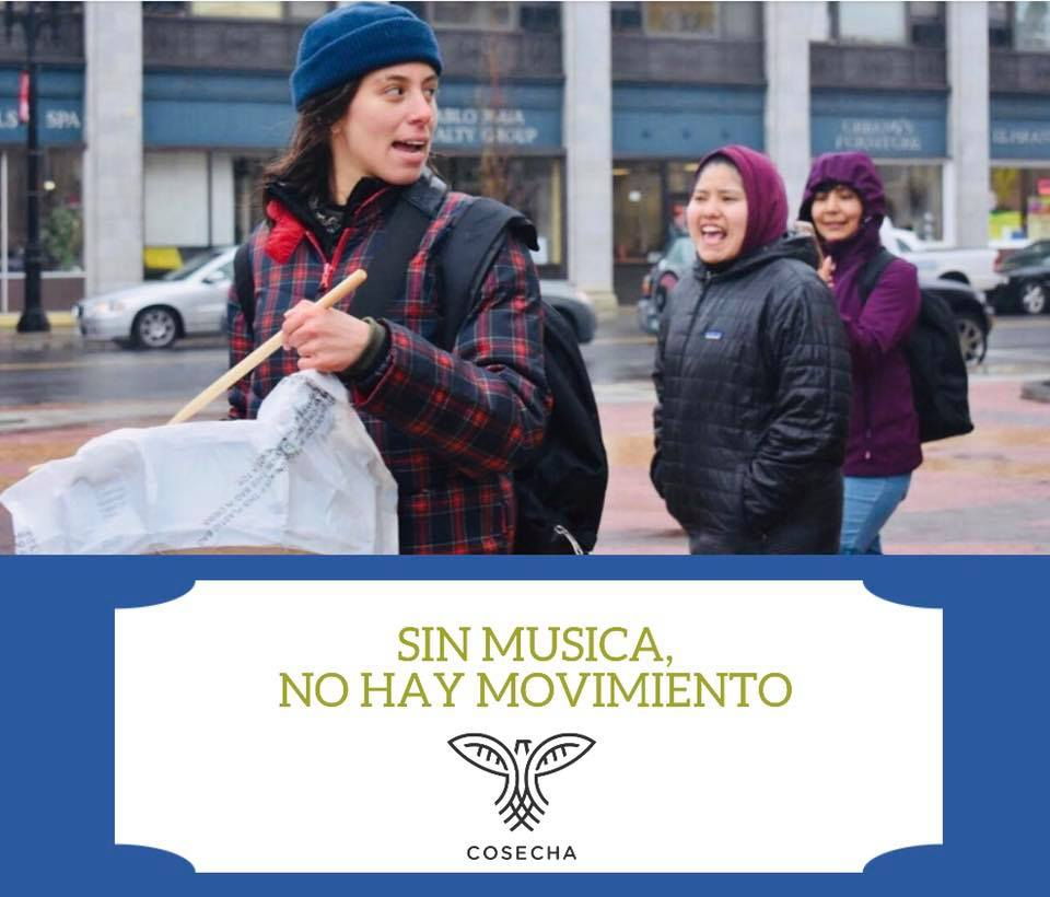 "Image description: Three Cosecha marchers walk down the street in Boston while chanting. The image is captioned by a blue banner and white box with the Cosecha logo and gold text reading ""SIN MUSICA, NO HAY MOVIMIENTO"" (""Without music, there's no movement"")"