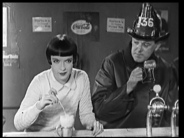Louise Brooks in  It's the Old Army Game (1926),  being paid close attention to by a local fireman at Pretty Willie's shop.