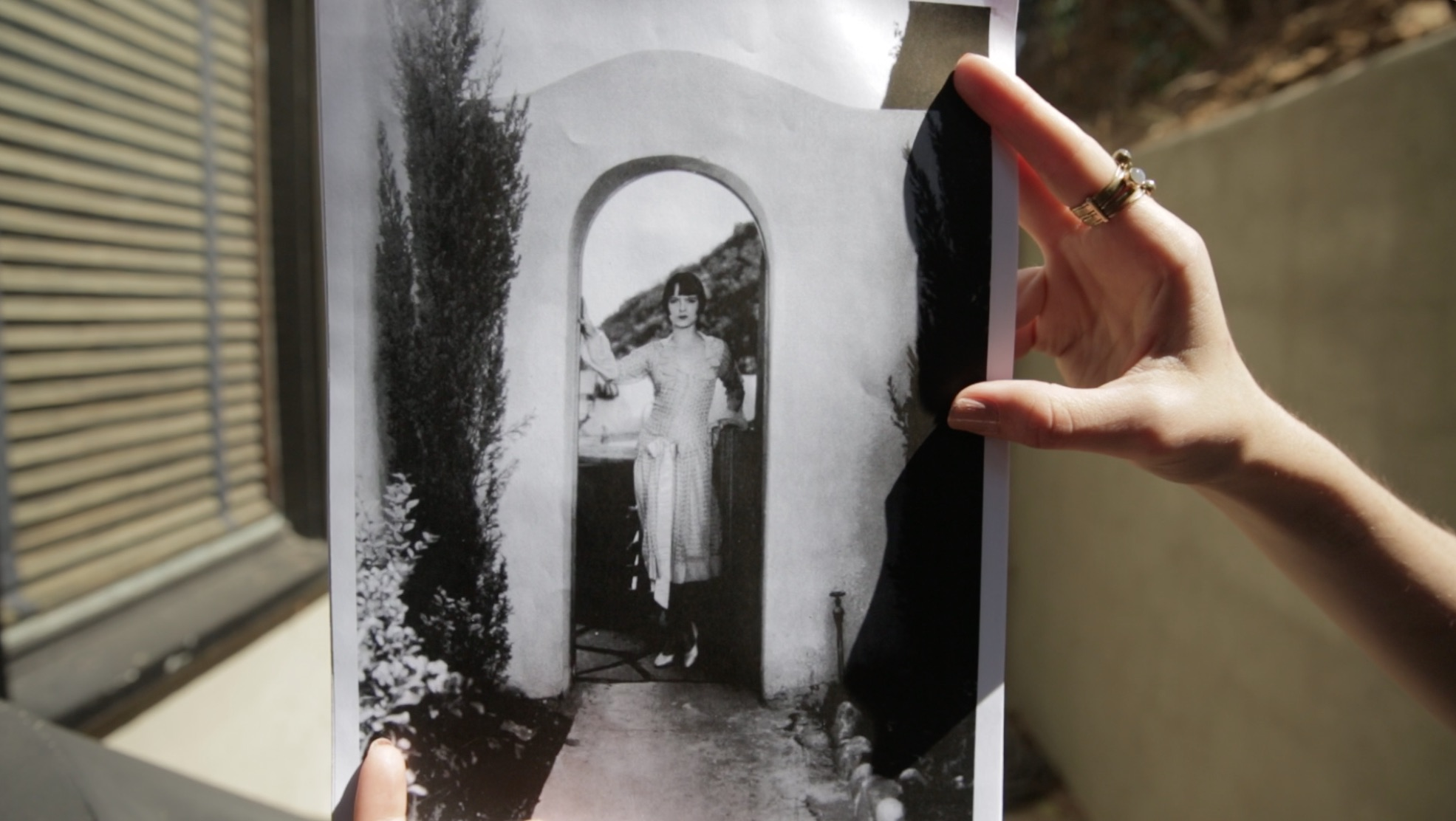 Then and Now: Louise posing in the archway of her home, one of the few places that hasn't been ravaged by time