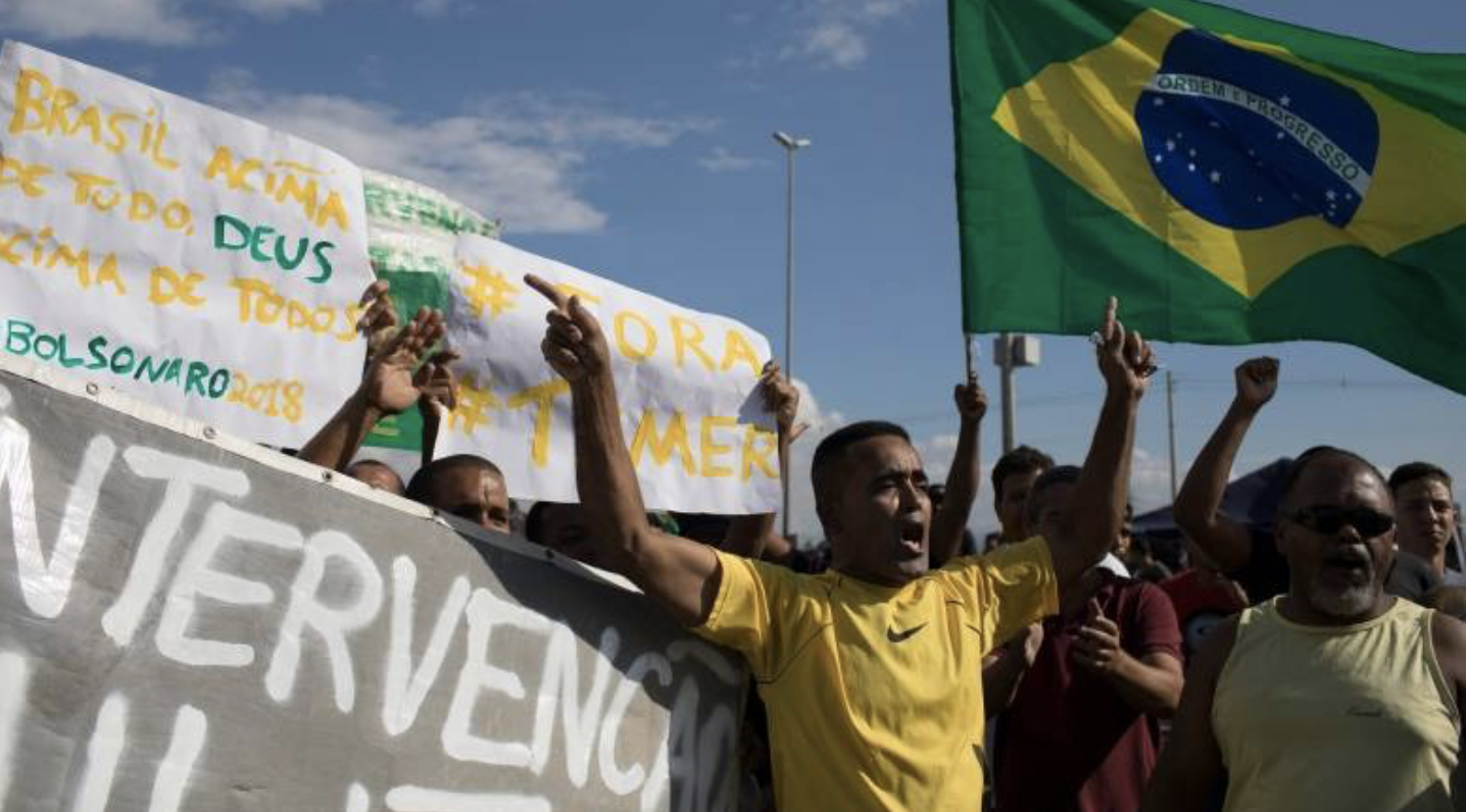 Striking truckers shout 'Get out Temer' on Monday as they protest rising fuel costs in front of a fuel distribution facility in Duque de Caxias, Brazil. The strike has caused shortages at gas stations and supermarkets across Latin America's biggest country.(Leo Correa/Associated Press)