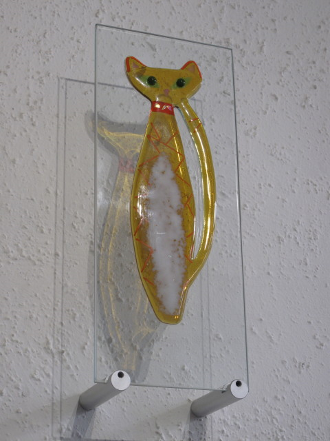 Amber Cat - £150.00 (ex brackets)  -   ENQUIRE NOW     15cm x 38cm - fused glass on plain glass pane   Each piece comes with it's own custom made wooden free standing base  The wall mounting brackets can be supplied for an additional cost