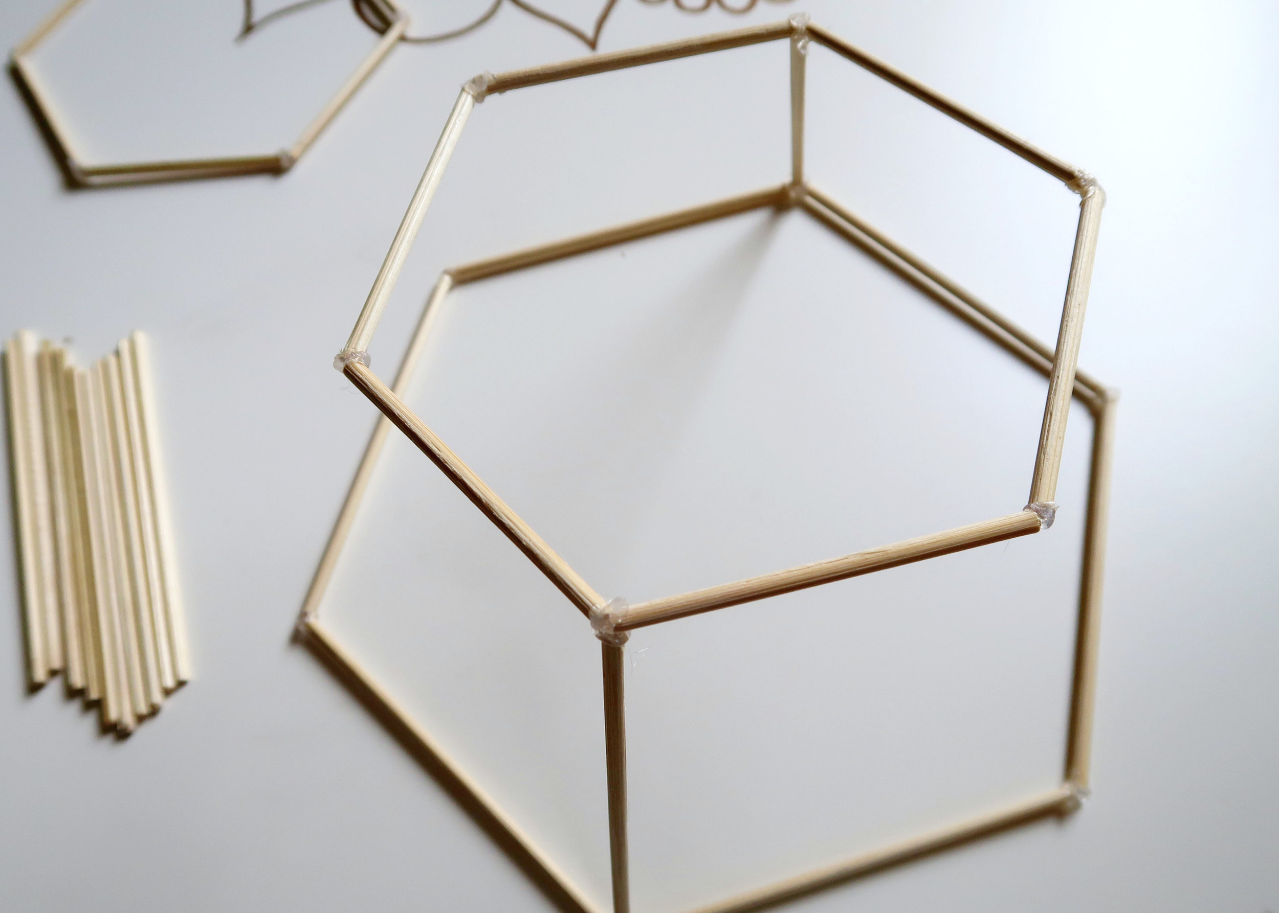 7. - Once dry, stick one of the small hexagons on top of the two 10cm skewers you just glued to the large hexagon. When these are secure, stick the other four 10cm lengths between the large and small hexagon at each angle.