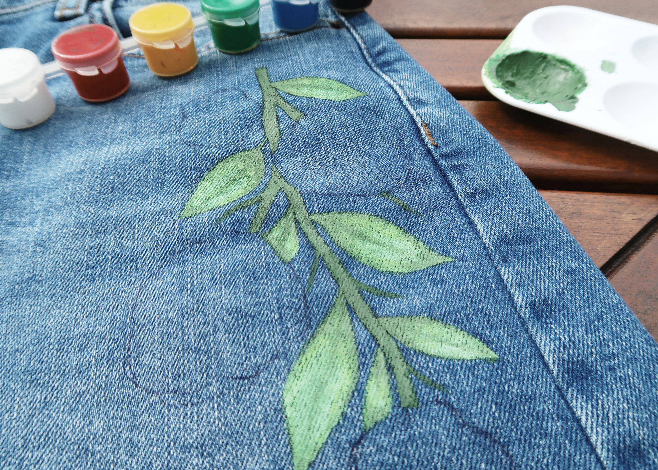 4. - Next, mix up a darker green and use this to paint the stems and to create some shadows on each of the leaves. Create an even darker green to add shadows to the stem. Using the white, add in some highlights.
