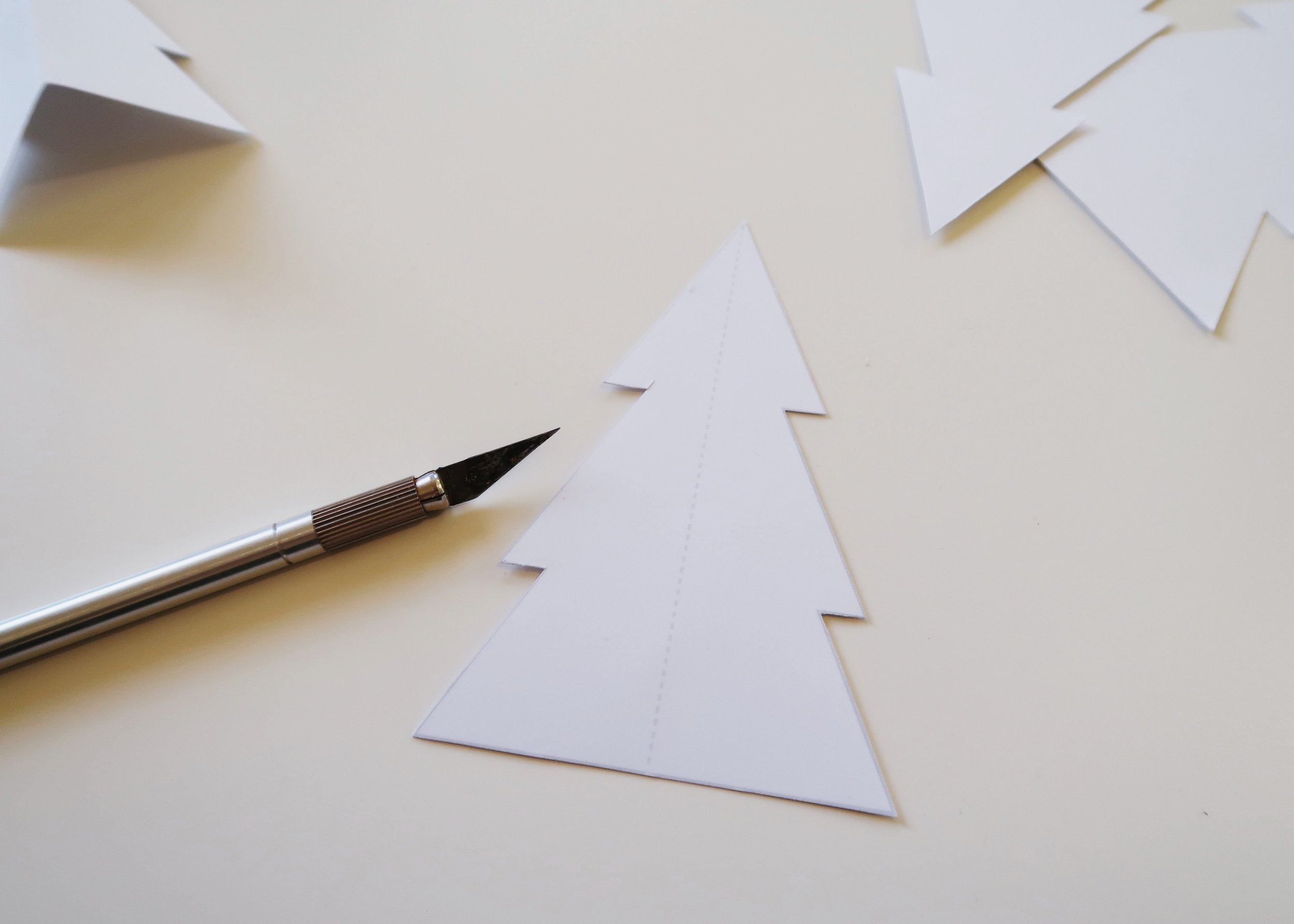2. - Using a ruler and a craft knife (or a pair of scissors), score down the dotted line in the middle of each of the trees. Be careful not to cut all the way through - you just want to make it easier to fold!