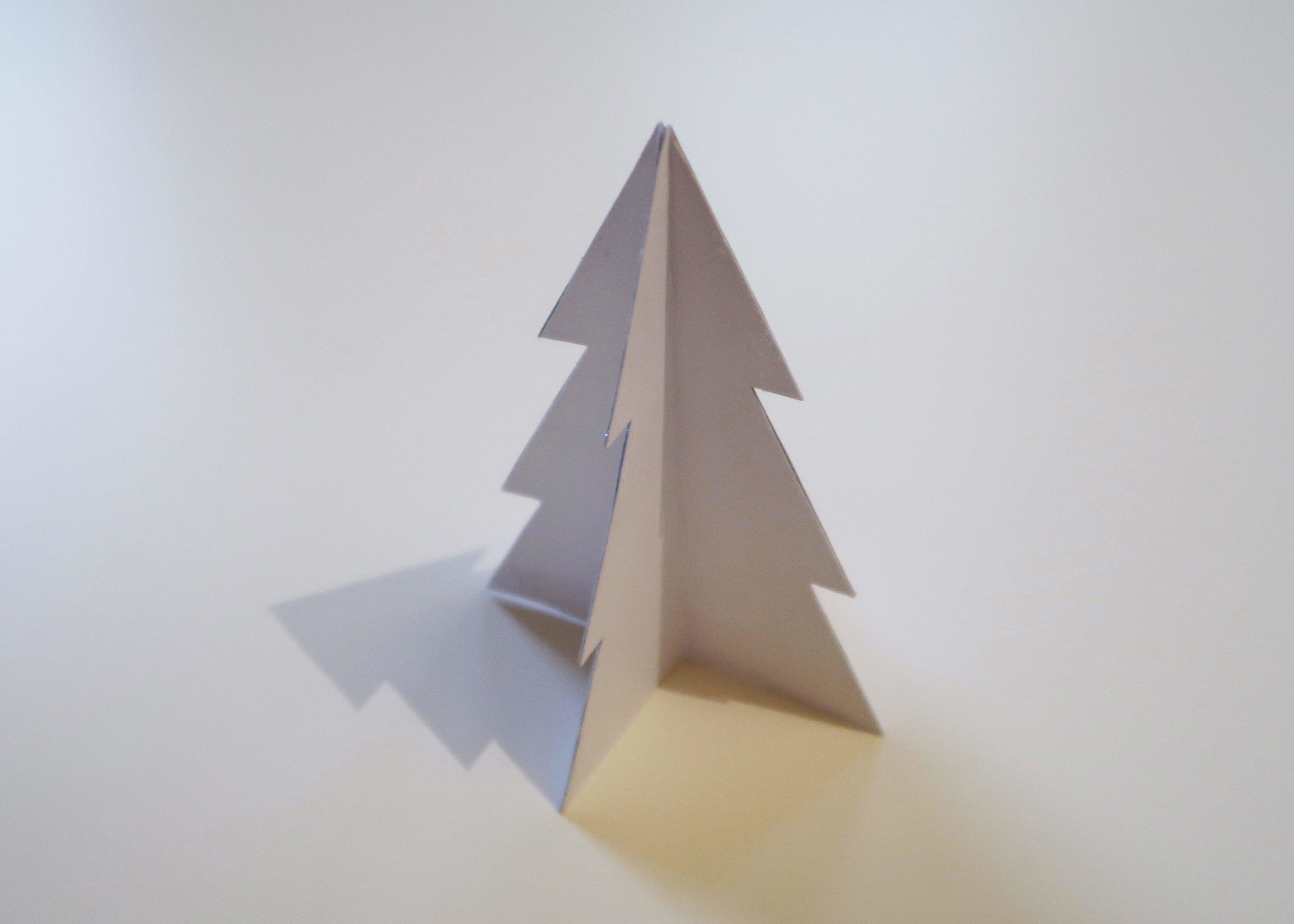 4. - Next, stick the trees together so that the dotted line is facing inwards. The easiest way to do this is to cover one half of one tree in glue and then stick one half of another tree to it and so on, until you've used all four trees and your now 3D tree is able to stand by itself.