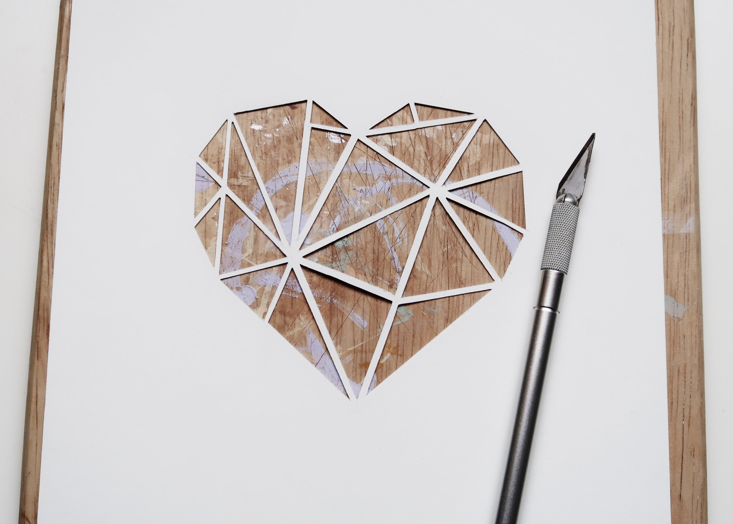 3. - Using scalpel and cutting board (or an old chopping board in my case), cut out each of the triangles within the heart, leaving the pencil lines in tact and connected to one another. The side with the pencil marks on will be the back.