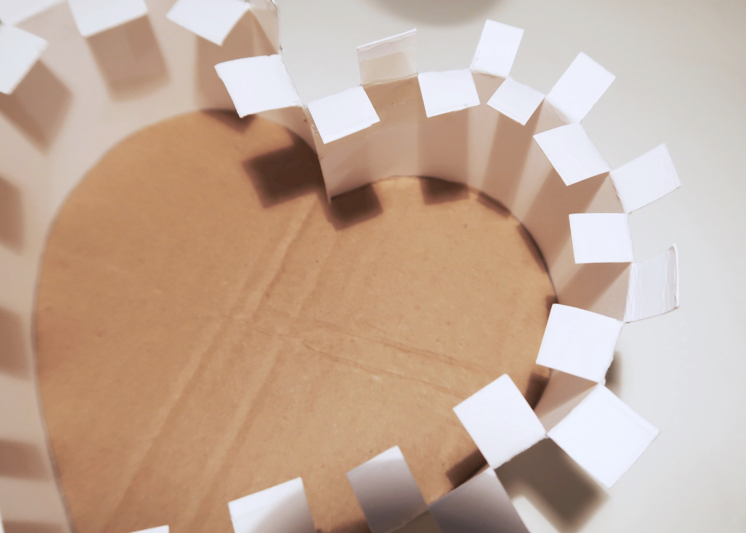 4. - Next, turn your pinata over so that the thinner cardboard sides are facing up. Using a pair of scissors, carefully cut into the sides by about 1cm and at 1cm intervals to form tabs. Fold every other tab towards the centre of the pinata.