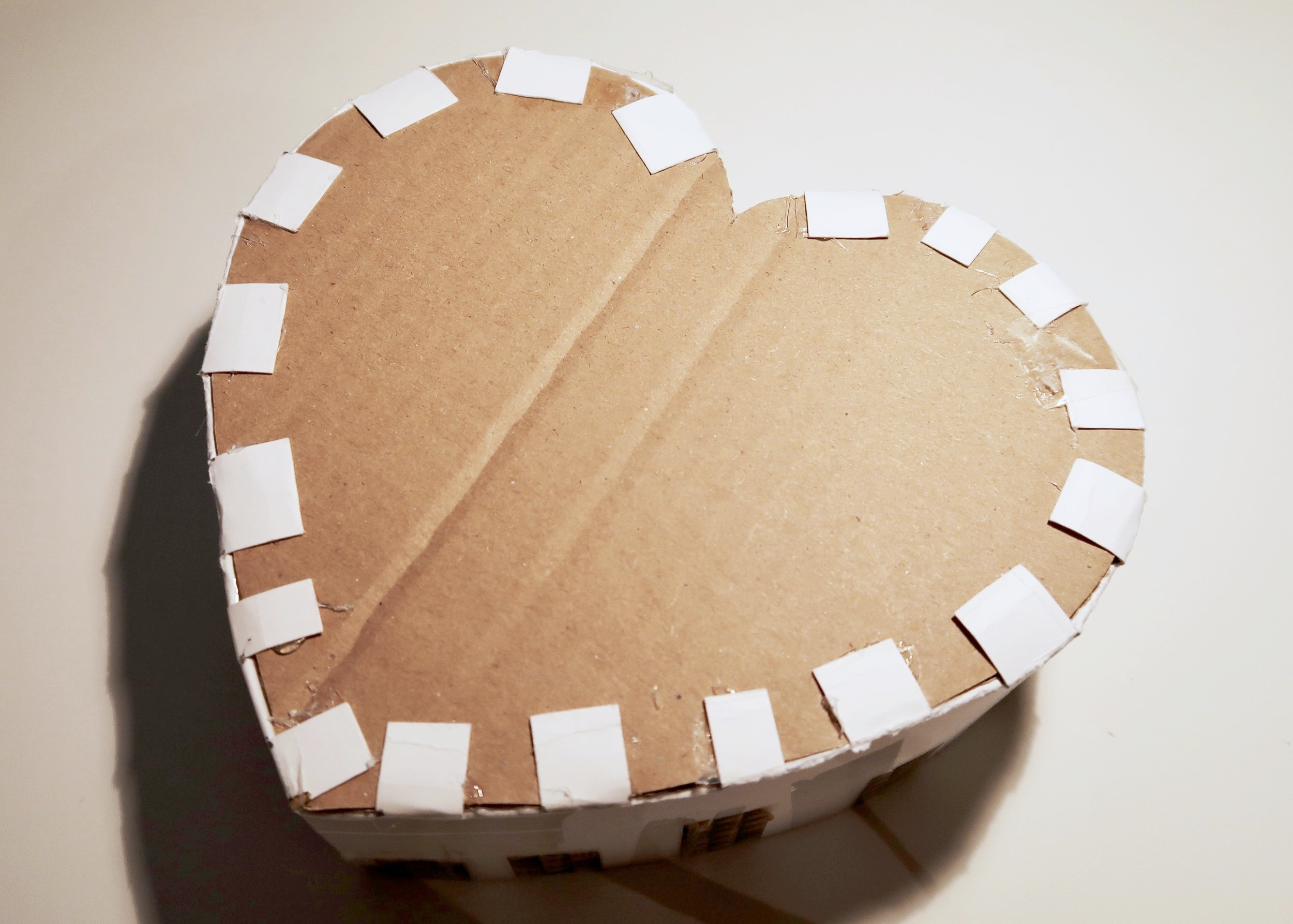 5. - Add hot glue to the tabs facing inwards, and glue the second cardboard heart on top of these. Now fold the remaining tabs towards the centre of the heart and using glue secure these to the top of the cardboard heart.