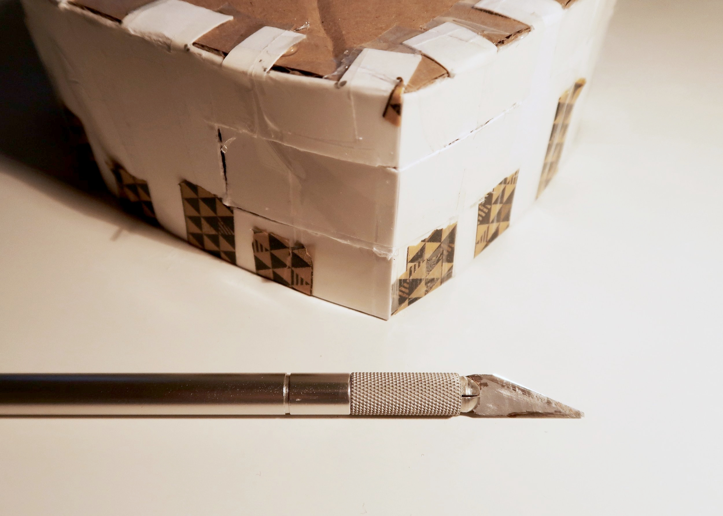 6. - Next, take a crafting knife and carefully cut a door into the base of your pinata. To do this, cut out a rectangle leaving one side uncut and attached to the box. Fold this side and add in your presents or sweets. Temporarily secure the door closed with a small bit of tape.