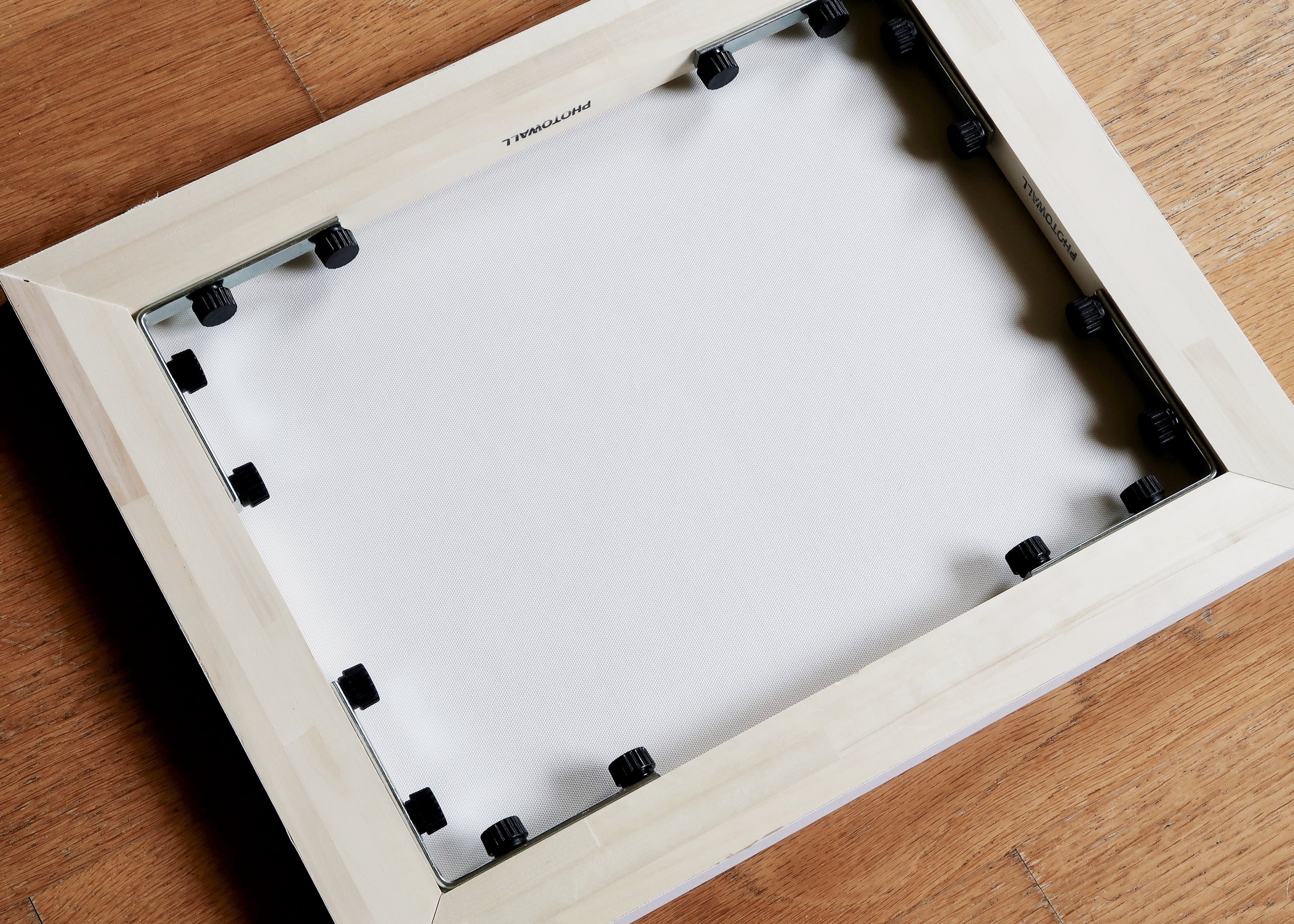 5. - Follow the instructions to stick each side of the wooden frame to the back of the canvas, before folding them in towards one another and securing them metal corner plates and screws. Photowall kindly do all the drilling and so all you have to do is twist the screws into the predrilled holes. Finally, wrap your gift or use the included hanging solution to get your canvas up on the wall!