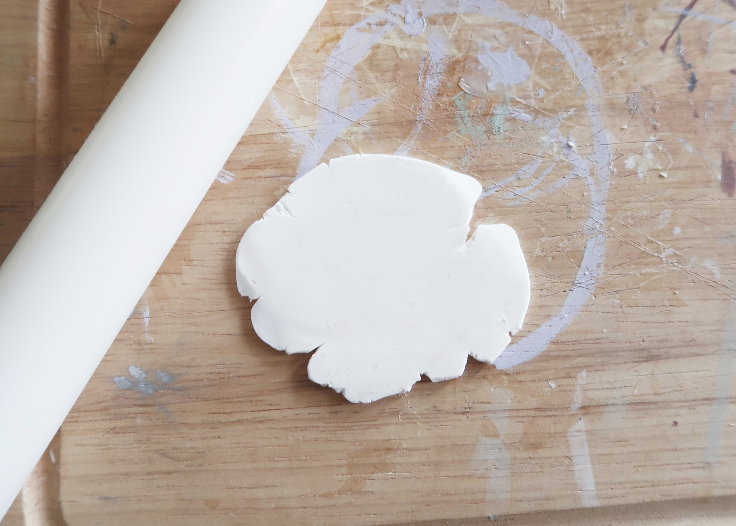 1. - First of all, knead some polymer clay in your hands until it is softer and more pliable. Roll out the clay until it is large enough and trace a round glass with your craft knife to cut out a circle from the clay.
