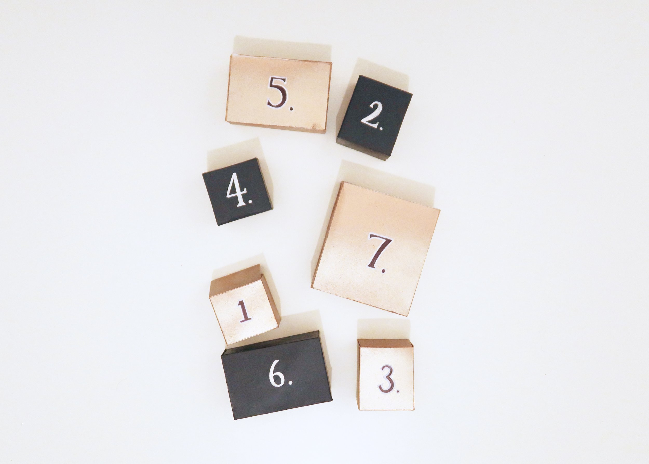4. - Once you're happy, take out the boxes and decorate them however you want. I chose to paint half in a navy blue, with white numbers drawn onto them (using the white gel pen), and the other half copper with black (using the sharpie) and white outlined numbers written onto them.