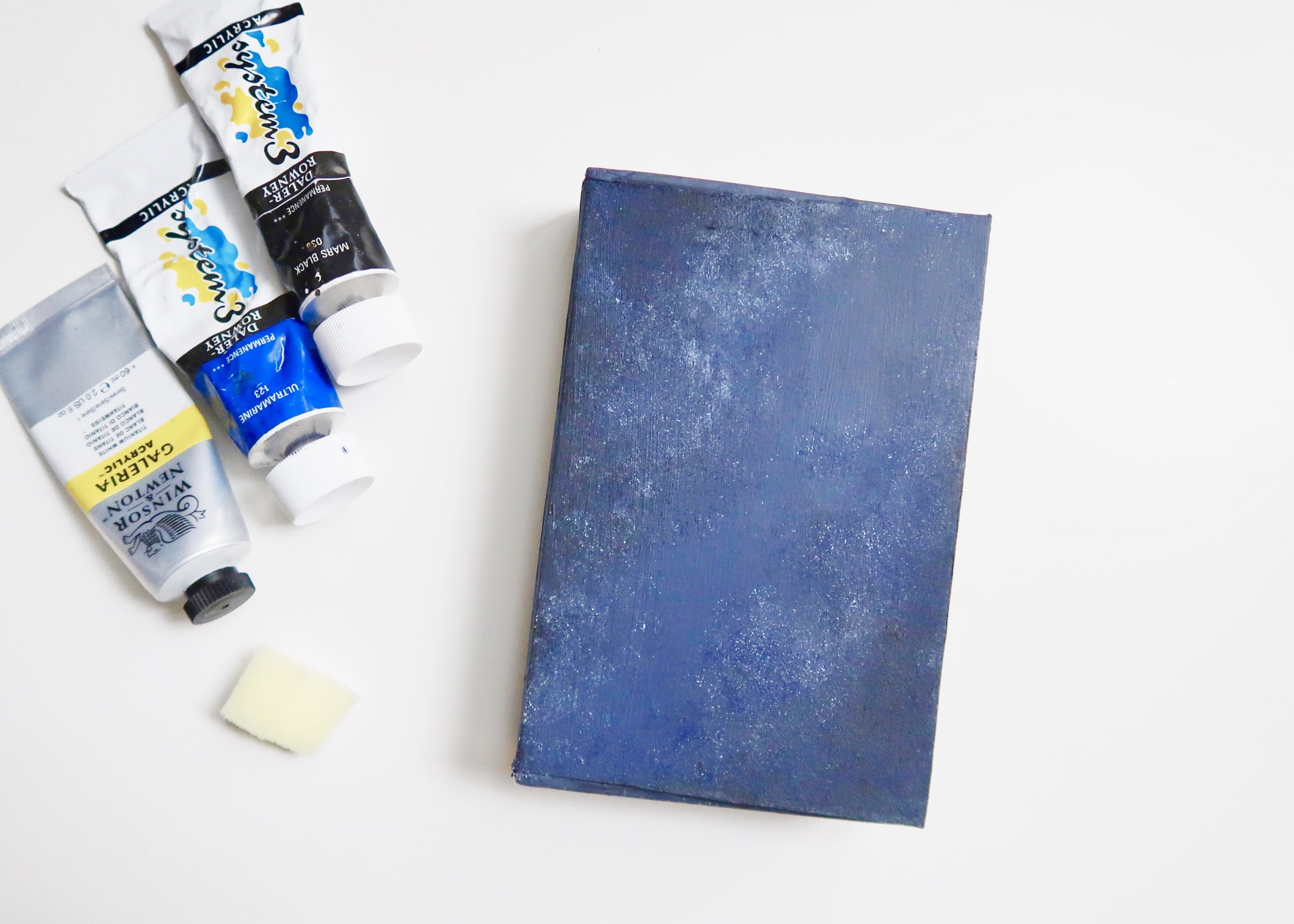 6. - To create the starry sky, use a sponge and a combination of white,  lighter blue and black acrylic paint. I found it helpful to start with the darker colours, and to build these up in the top left and bottom right hand corners, leaving a gap from the top right to the bottom left. Add some white to the same sponge, and carefully add some white at the edges of the darker blue in the corners, to look a bit like clouds. Keep building it up until you're happy. Once you are, leave it to completely dry.