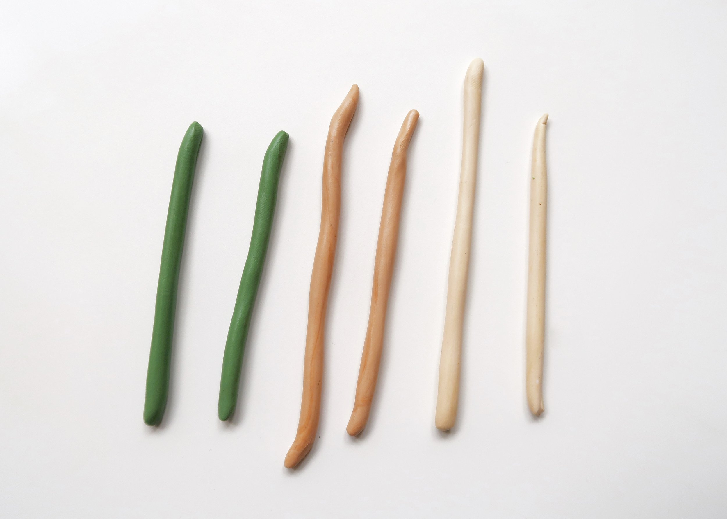 2. - Once you're happy with the colour of each of the clay balls, cut them in half. Using your hands and a non-sticky work surface, roll each ball into tubes of approximately the same diameter. Don't worry about the length of the tubes, the most important thing is that they are roughly the same width.