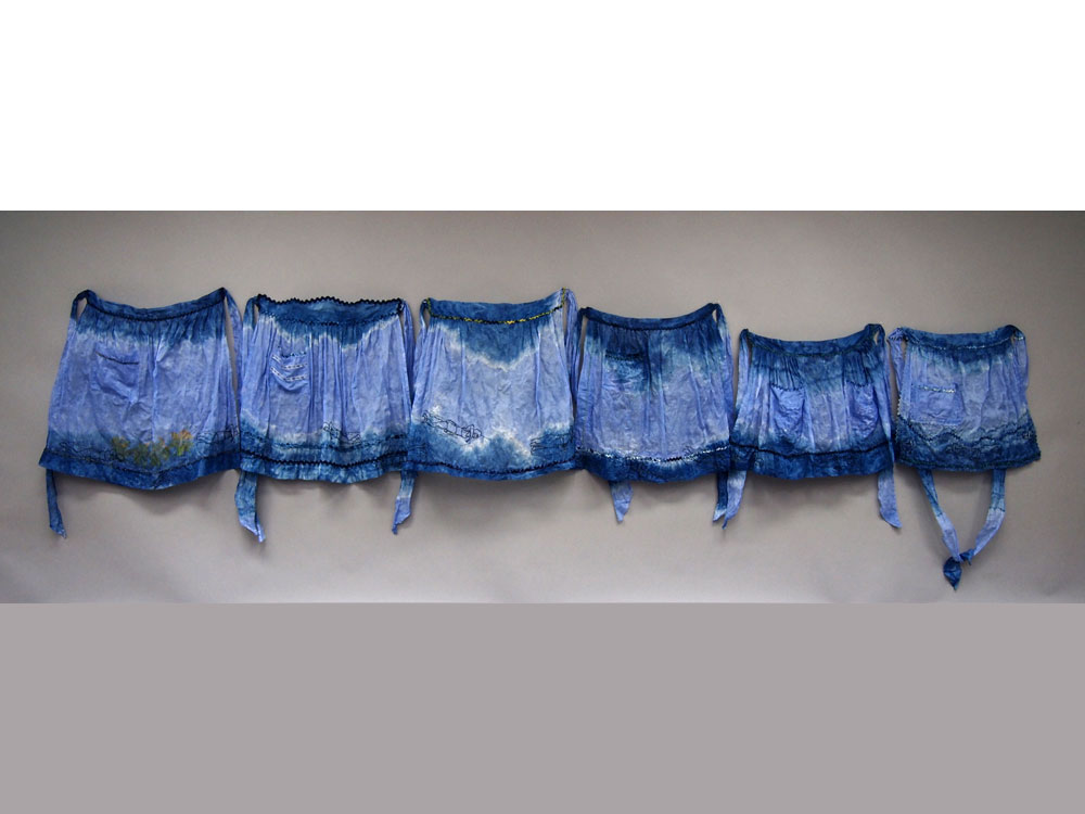 Laps  2014 discharge (indigo) dyed vintage cotton organdy aprons and ric-rac, hand stitched and embroidered