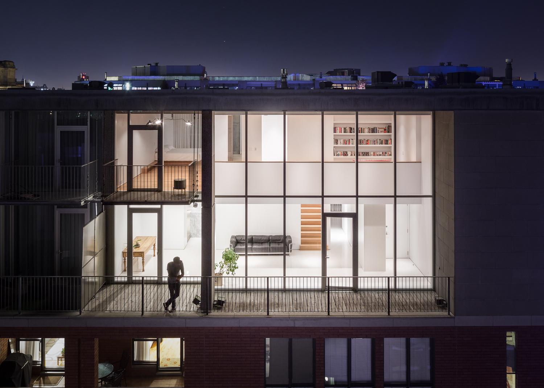 Vue extérieure du penthouse situé dans le Vieux-Montréal. Façade entièrement vitrée. Rdc majoritairement blanc et étage avec bibliothèque sur mesure et plancher de bois
