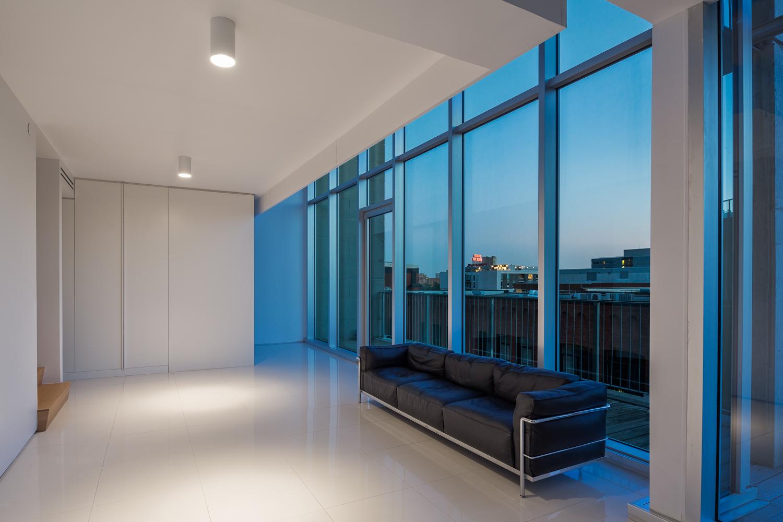 Salle de séjour avec canapé 3 places noir LC2 Le Corbusier. Grande fenestration à l'arrière donnant la vue sur Montréal. L'intérieur, totalement blanc, est éclairé par 2 cylindres blancs
