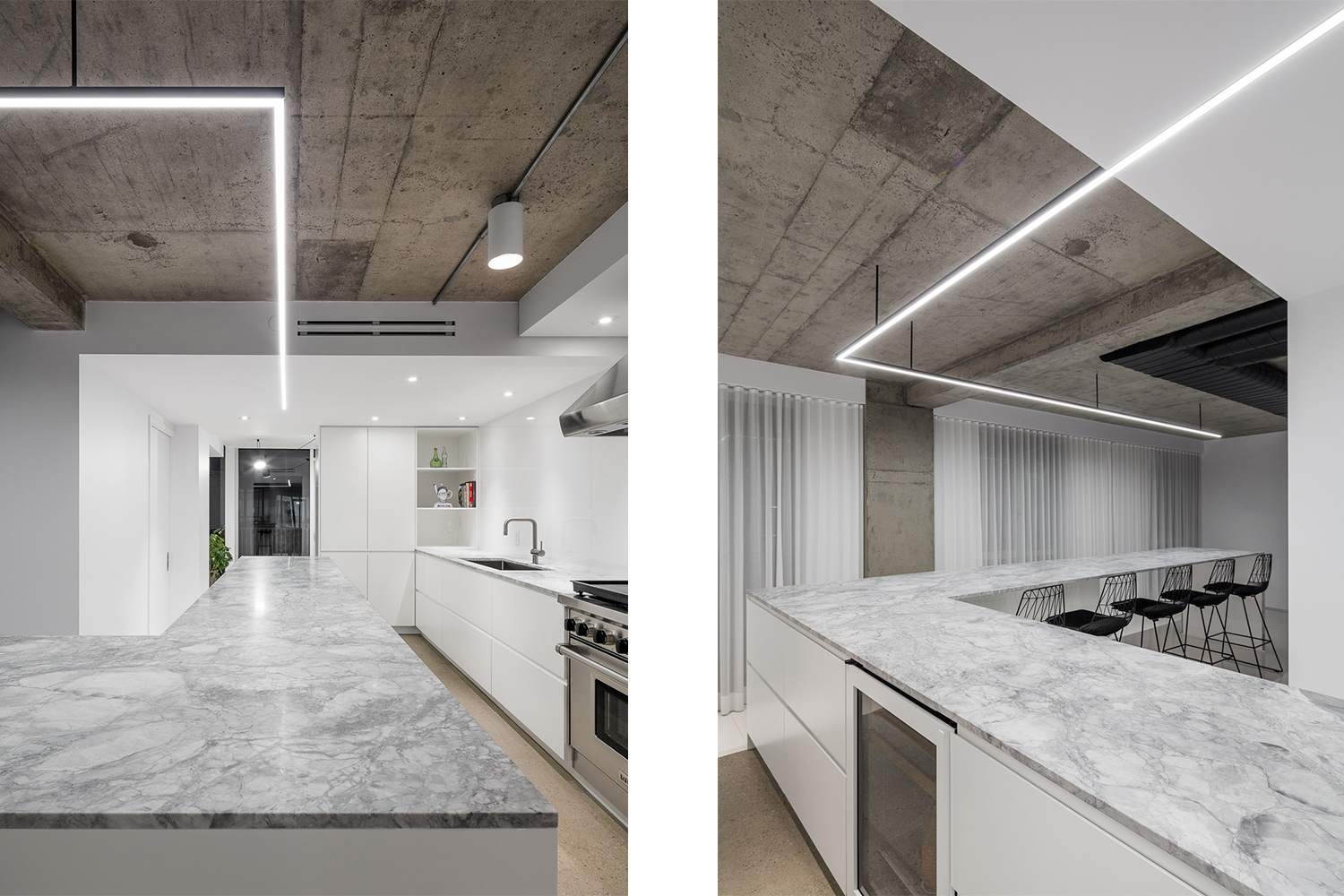 L-shaped kitchen with very large statuario marble countertop. Lacquered white lacquered kitchen cabinet with integrated handle. A linear LED luminaire following the countertop is suspended from the concrete ceiling