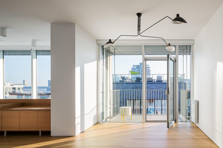 Espace avec porte vitrée ouverte donnant sur un balcon. Luminaire 3 bras de Serge Mouille au centre de la pièce. Petite table Retailles jaune fabrication La Firme. Plancher de l'étage en chêne blanc
