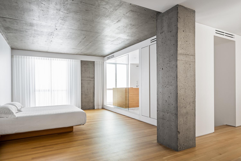 Vue en coin de la chambre principale avec plancher de chêne blanc, plafond de béton et lit king blanc. Grande colonne de béton délimitant la salle de bain. Voilage léger blanc couvrant les fenêtres
