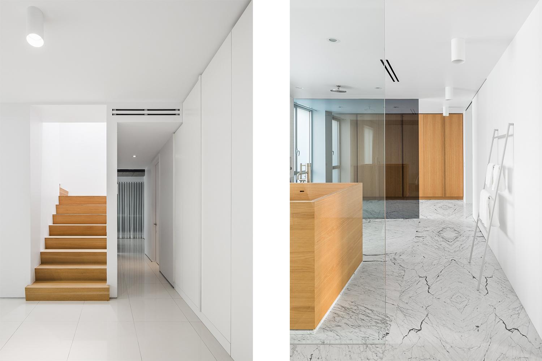 Vue sur l'escalier fait en chêne blanc menant à l'étage. Autre vue sur salle de bain avec plancher de marbre statuario. 2 grandes parois de verre délimitent l'espace. Baignoire en bois