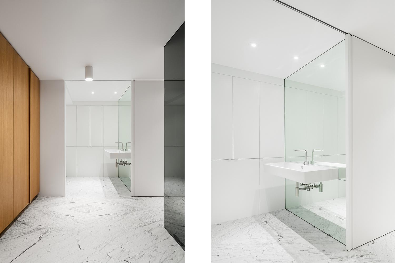 Salle de bain avec plancher de marbre statuario. Lavabo mural installé sur un miroir plein hauteur. Mobilier de rangement intégré fini chêne blanc.