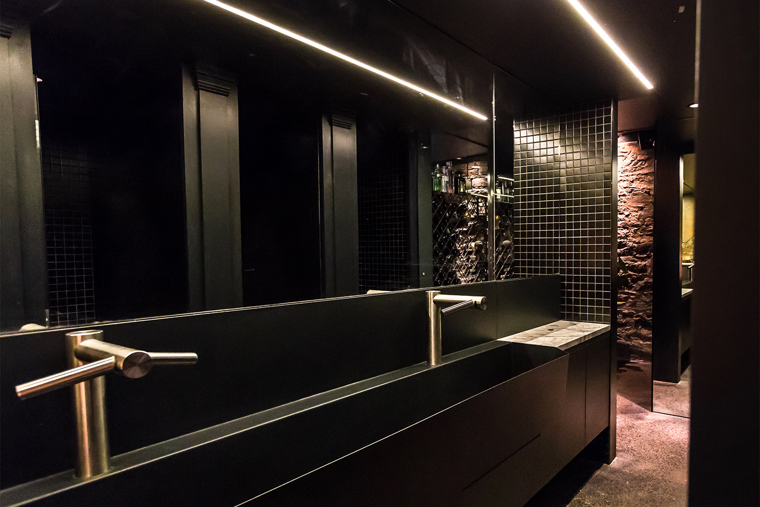 Black commercial bathroom. Automatic faucets installed on the washbasin made to measure in black finish metal. A large mirror with a black mosaic section gives us a glimpse of the cabins