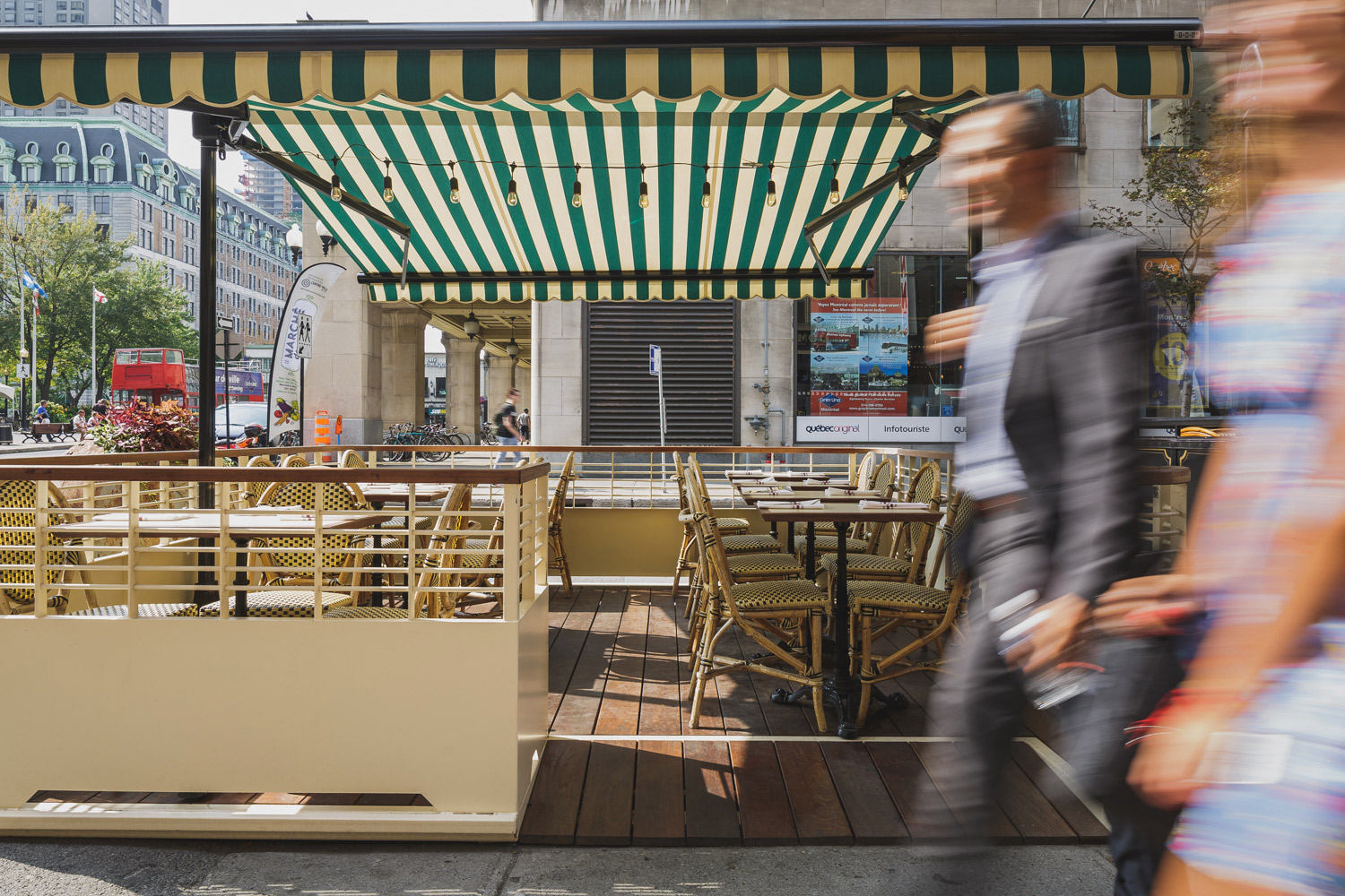 Outdoor terrace of a restaurant in downtown Montreal. Awning in white and green canvas with structure built in Ipe and white painted steel by hand.