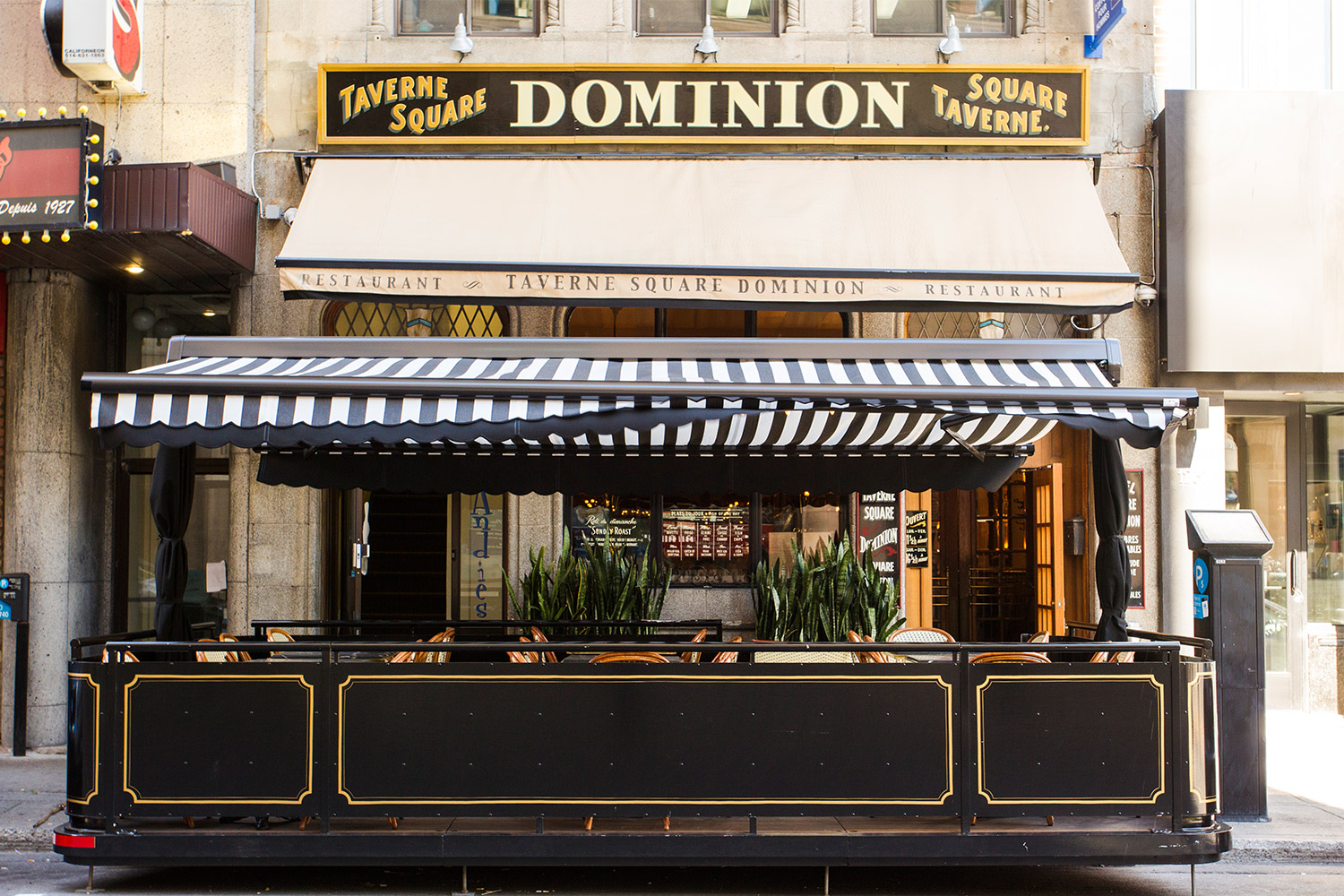 Outdoor terrace of a restaurant in downtown Montreal. Awning in white and black canvas with structure built in Ipe and black painted steel. Art Deco hand-painted gold moldings