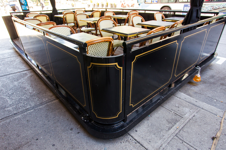 Terrasse extérieur démontable en aluminium d'un restaurant au centre-ville de Montréal. Table en marbre noir avec chaise bistrot parisienne. Moulures Art déco dorées peintes à la main
