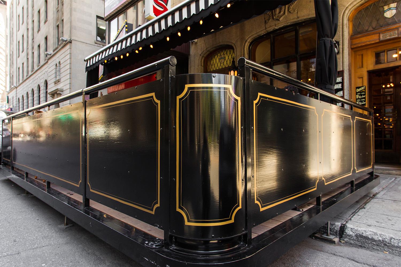 Vue en contre-plongée du garde-corps de la terrasse du restaurant. Panneaux verticaux en aluminium peint noir avec moulures d'inspiration Art déco dorées peintes à la main.