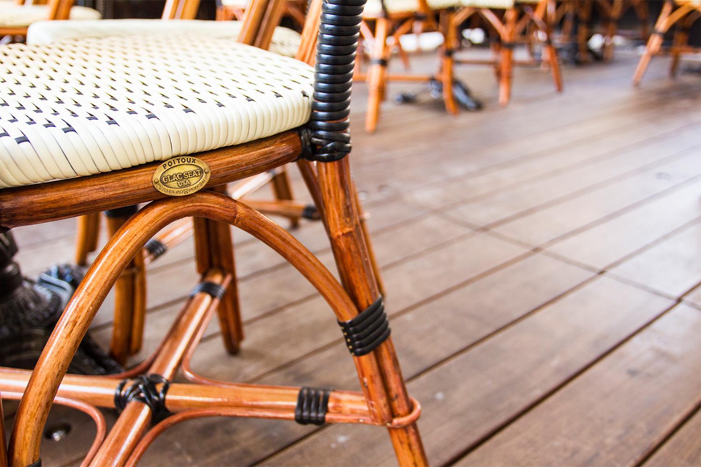 Vue détaillée d'une chaise de terrasse sur plancher de bois d'ipé. Structure de la chaise en bois assemblée avec rotin tissé. Cannage majoritairement blanc et détail noir.